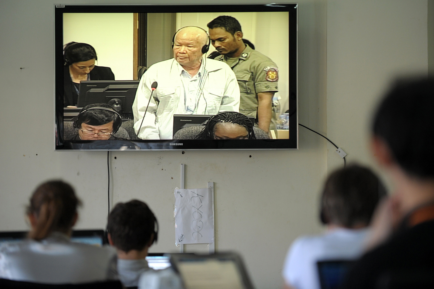 Cambodian and international journalists watch a live video feed showing former Khmer Rouge head of state Khieu Samphan during a hearing for his trial at the Extraordinary Chamber in the Courts of Cambodia in Phnom Penh on Jan. 8, 2015