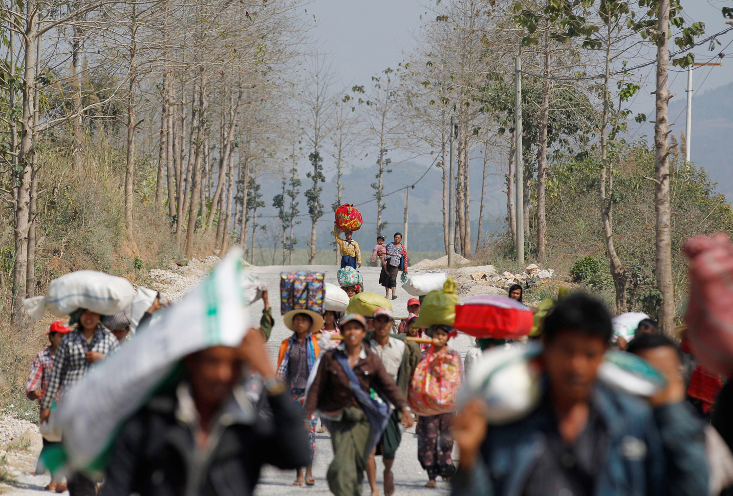 People displaced by the fighting in Burma's Laukai approach a rescue convoy on Feb. 17, 2015