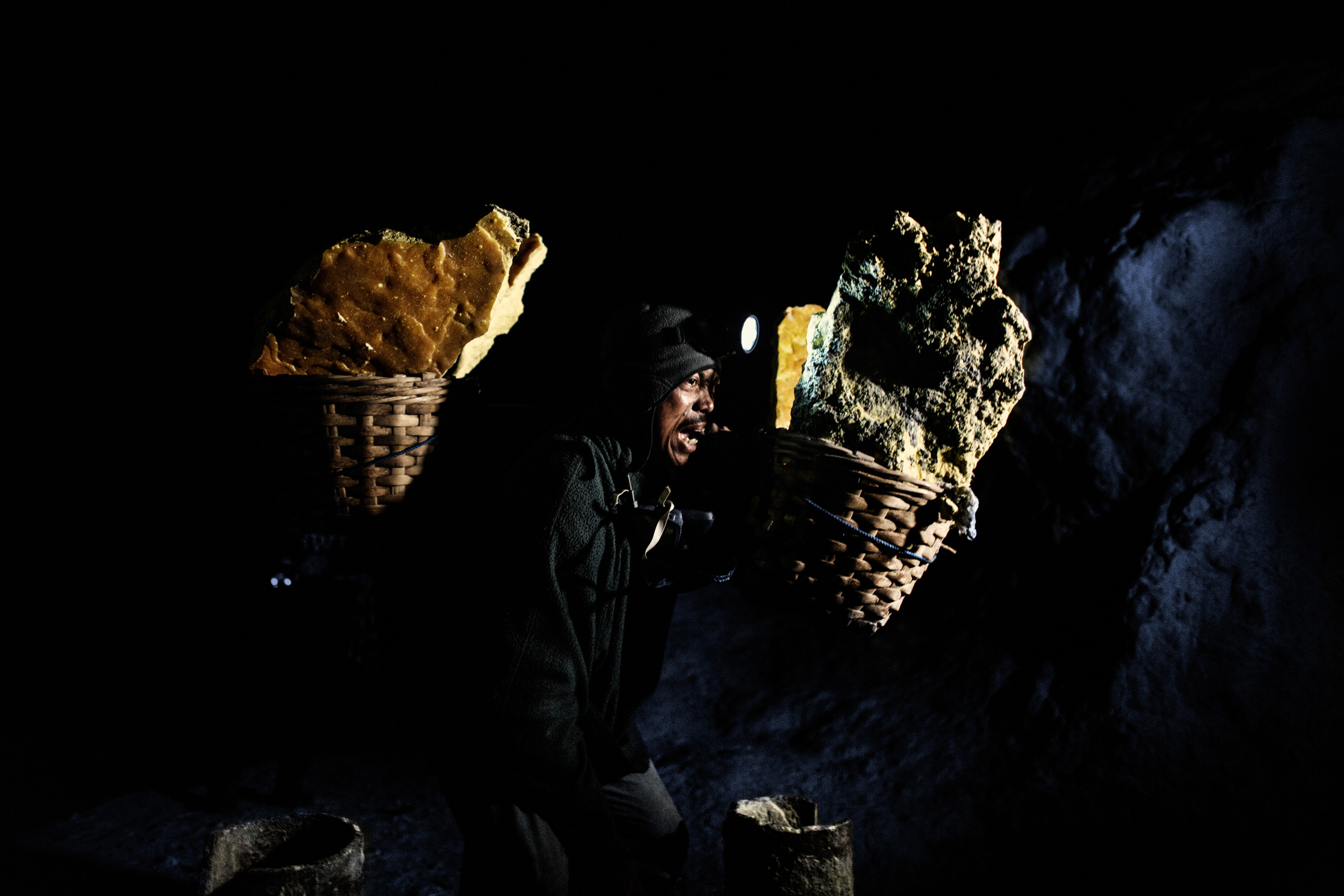 Matsari, 39, a sulfur miner for 10 years, carries the fully loaded baskets on his shoulders,  Nov. 2, 2014.