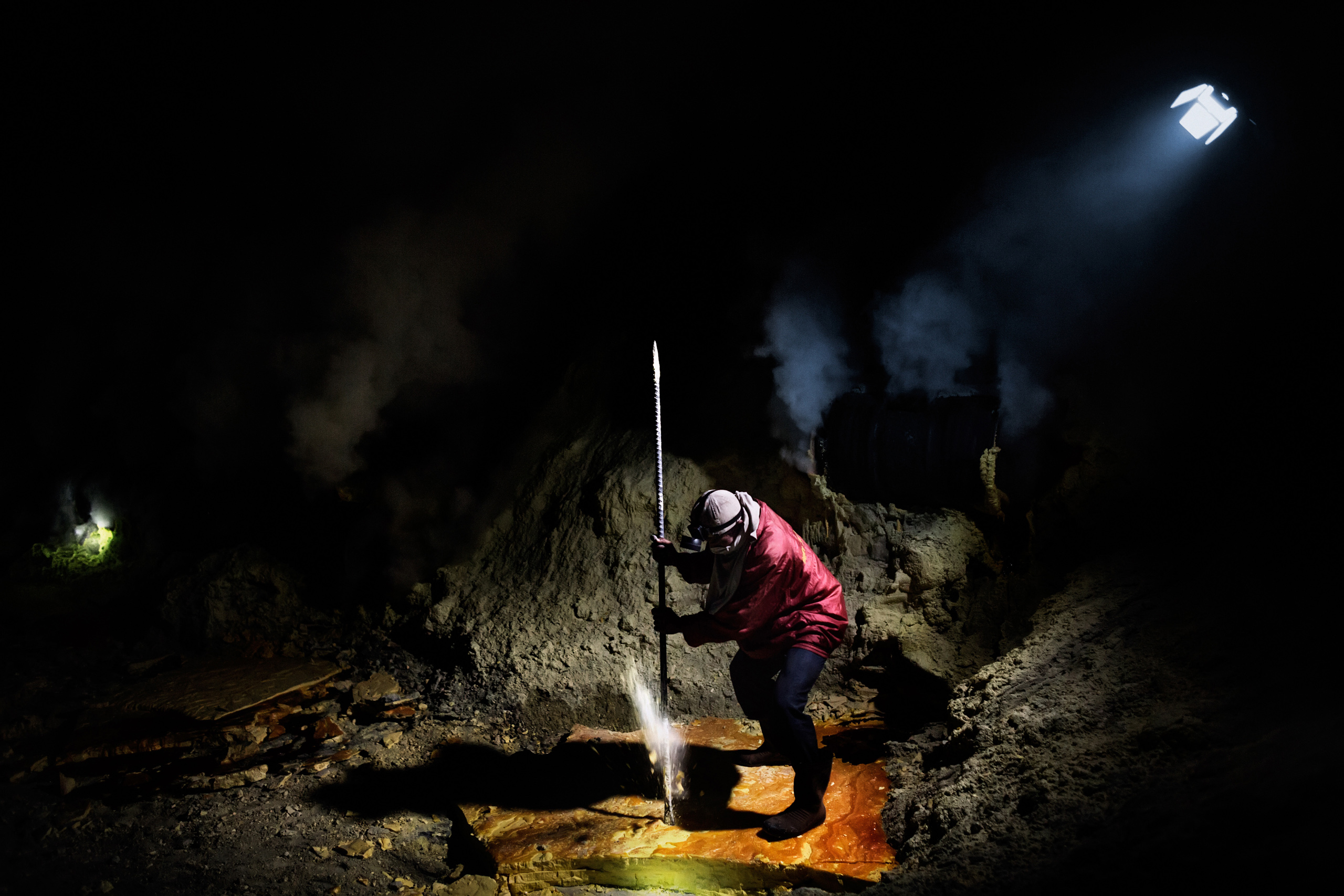 Poniman, 35, breaks the sulfur slabs using a metal pole, Nov. 2, 2014.