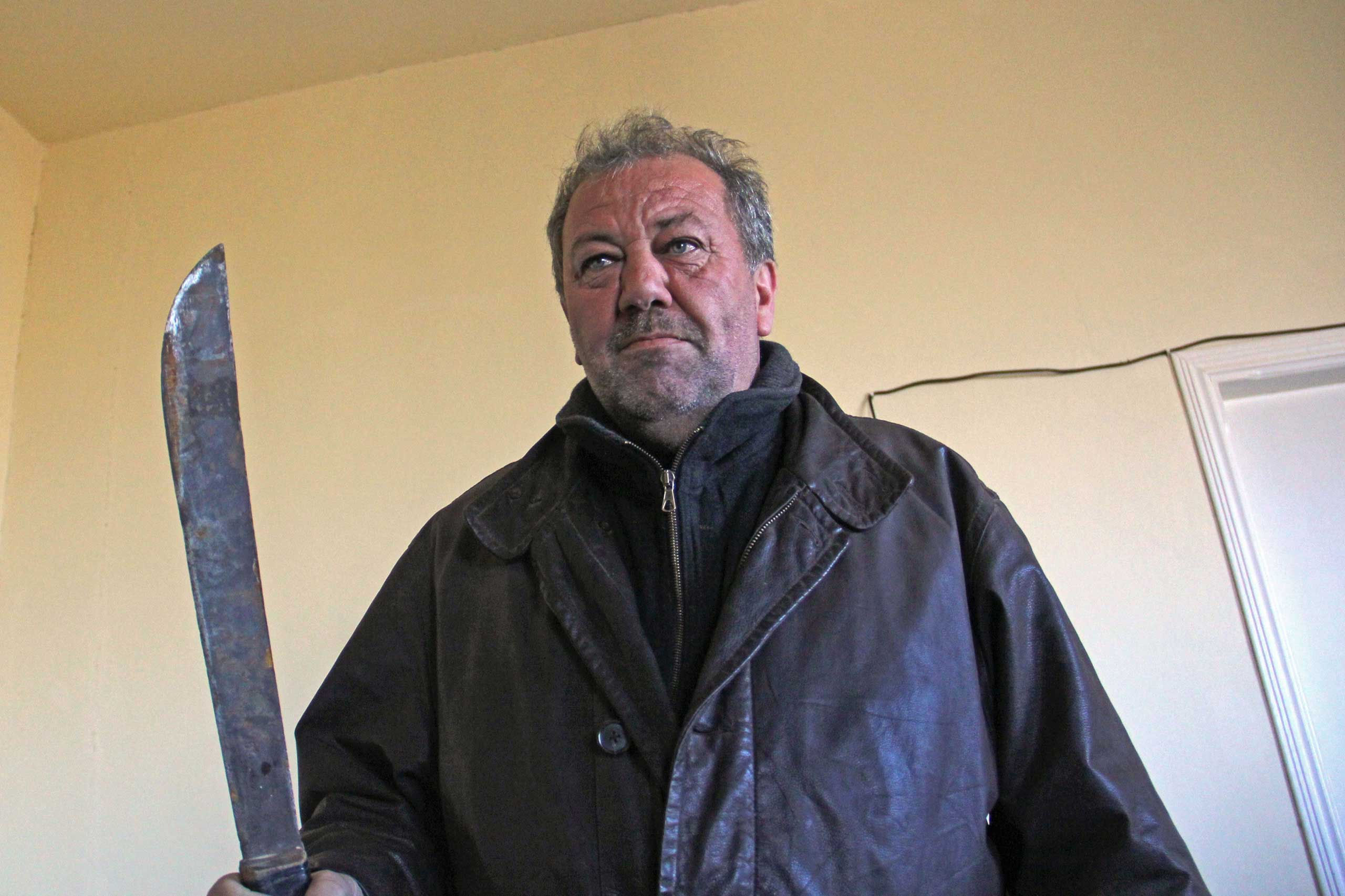 Hash dealer Ali Nasri Shamas holds up a machete he promises to use on jihadis.