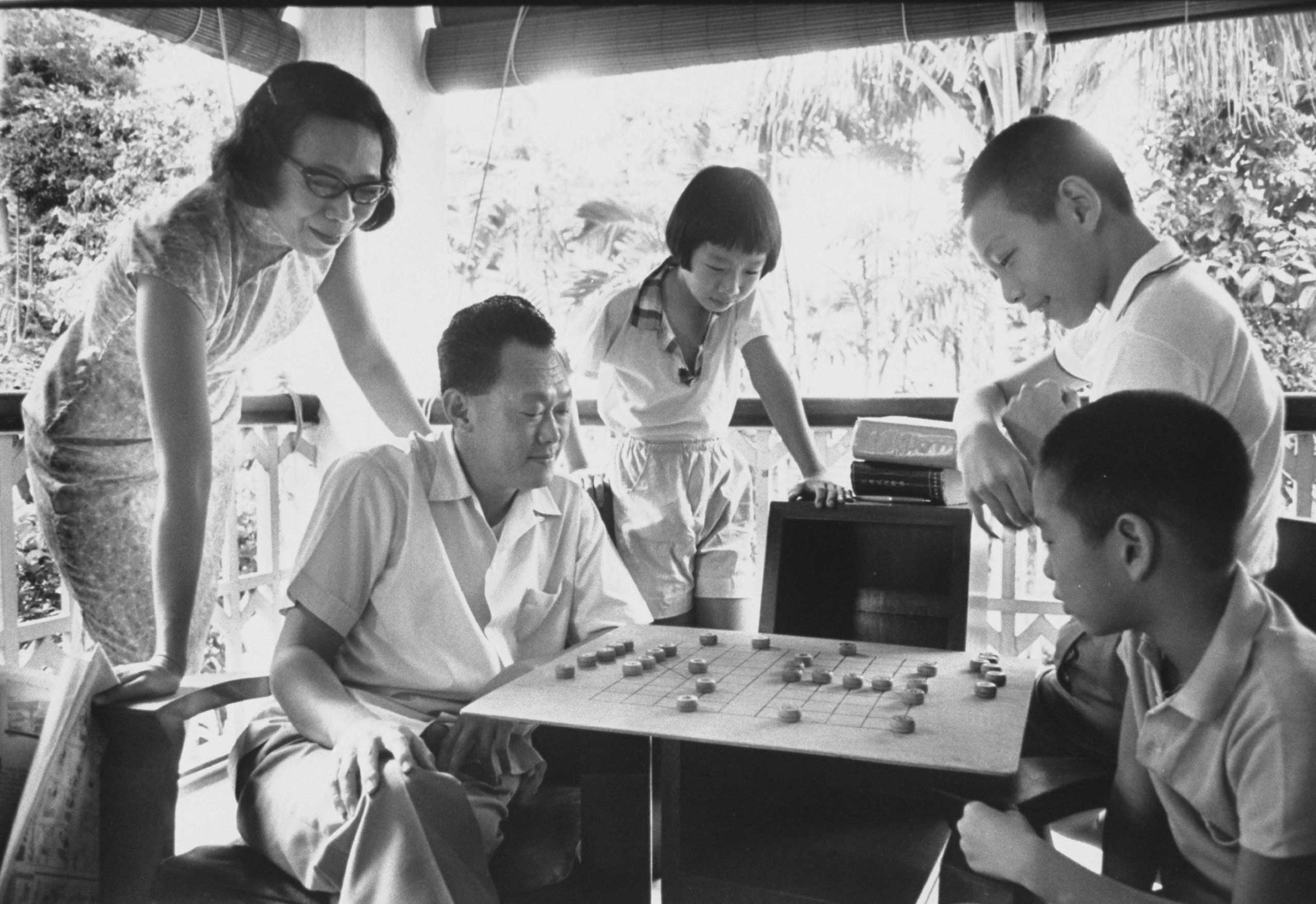 Prime Minister Lee Kuan Yew at home with his family playing Chinese chess in 1965.
