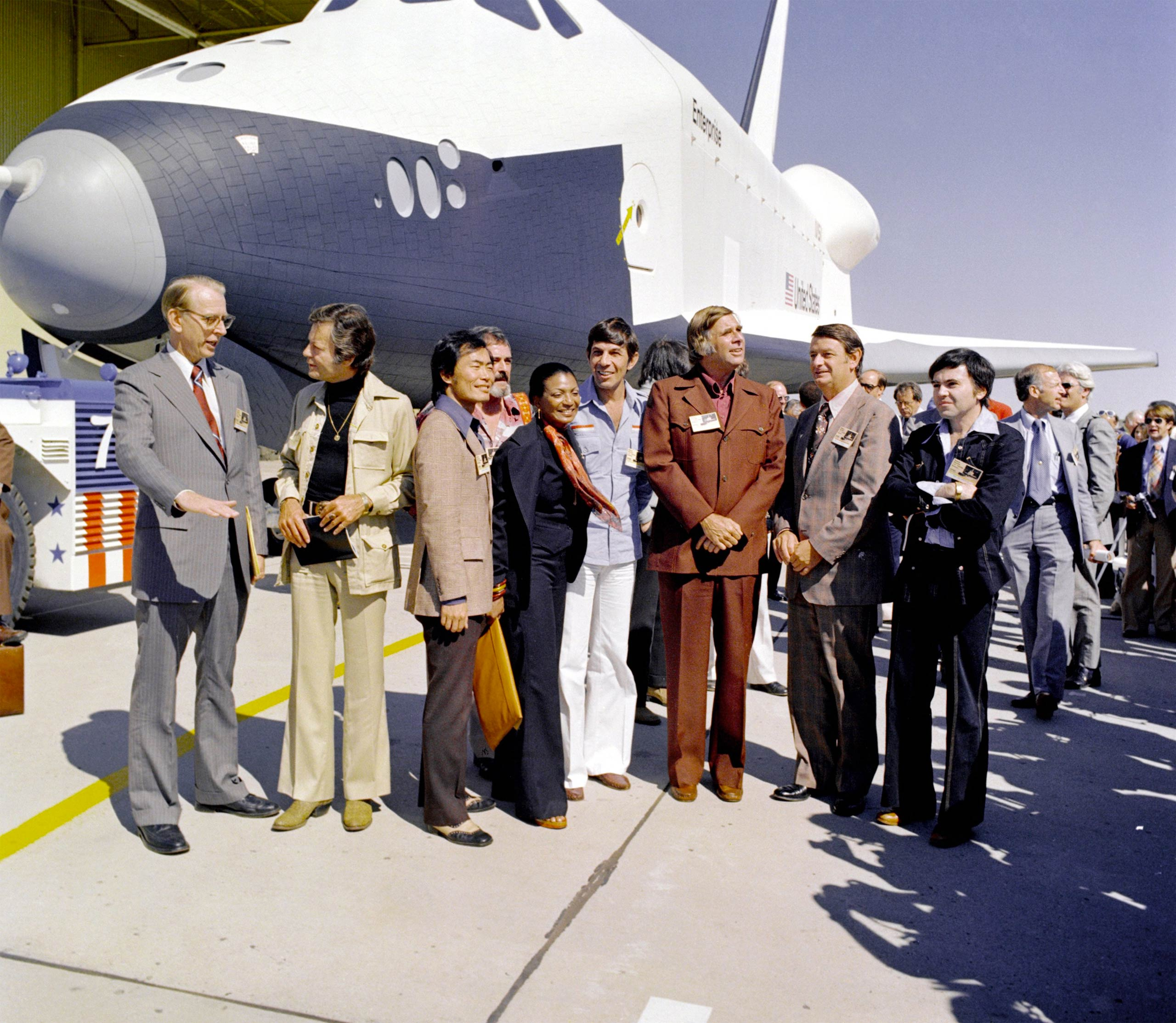 "NASA's space shuttle Enterprise rolled out of the Palmdale manufacturing facilities and was greeted by NASA officials and cast members from <i> Star Trek</i> in 1976. From left: NASA Administrator Dr. James D. Fletcher; DeForest Kelley, who portrayed Dr. ""Bones"" McCoy on the series; George Takei (Mr. Sulu); James Doohan (Chief Engineer Montgomery ""Scotty"" Scott); Nichelle Nichols (Lt. Uhura); Leonard Nimoy (Mr. Spock); series creator Gene Roddenberry; an unnamed NASA official; and, Walter Koenig (Ensign Pavel Chekov)."
