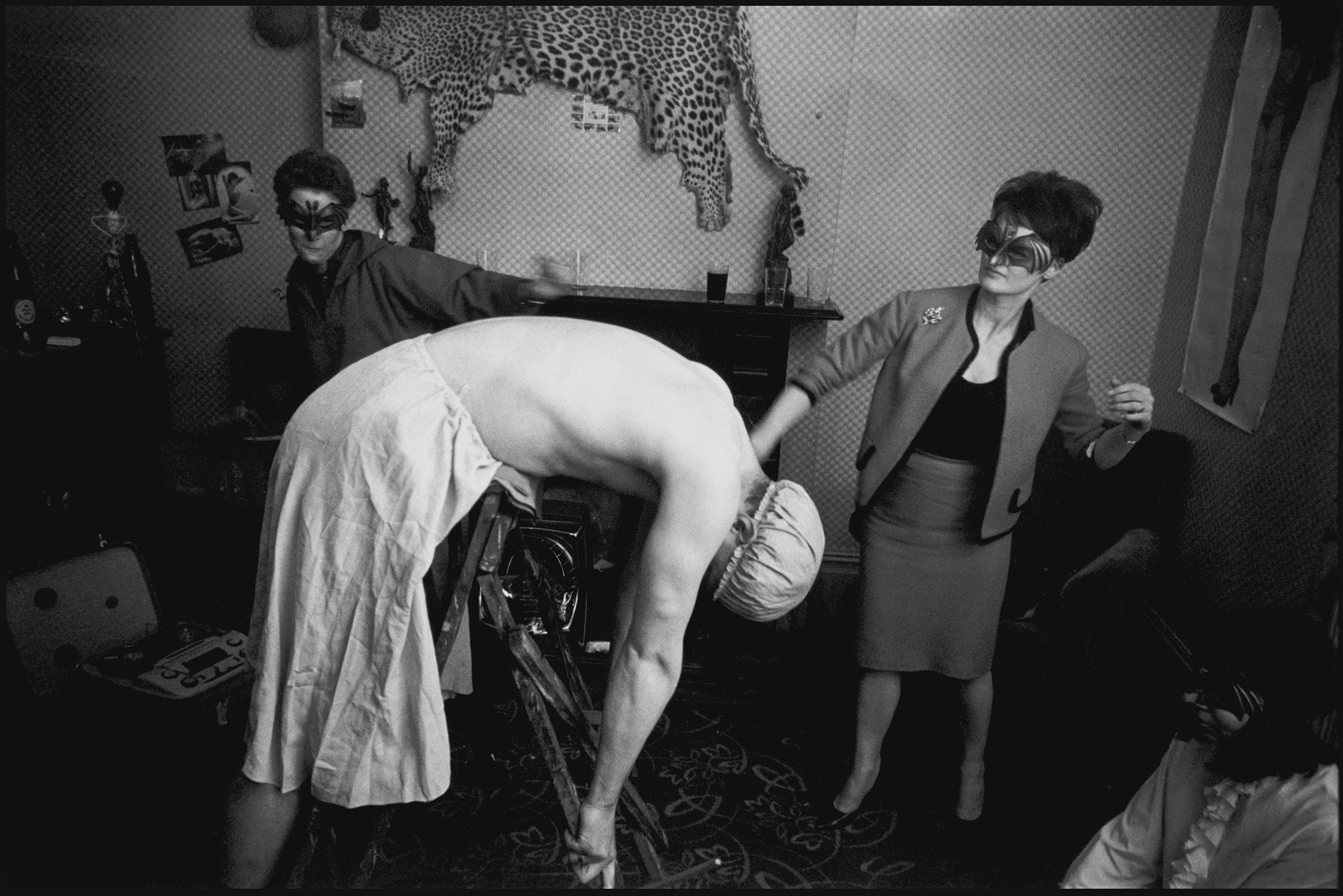 A Lesbian wedding in London. The man  in the photo had apparently insulted one of the women, by falling in love with her and asking her to marry him. He had to be punished. He would come to the wedding for his wipping and bring his own whips. He was photographed in a bathing cap, childs rubber training pants and a petticoat, being whipped by the bridal pair after which the girl he loved walked on his belly in stiletto heels. London, 1965.