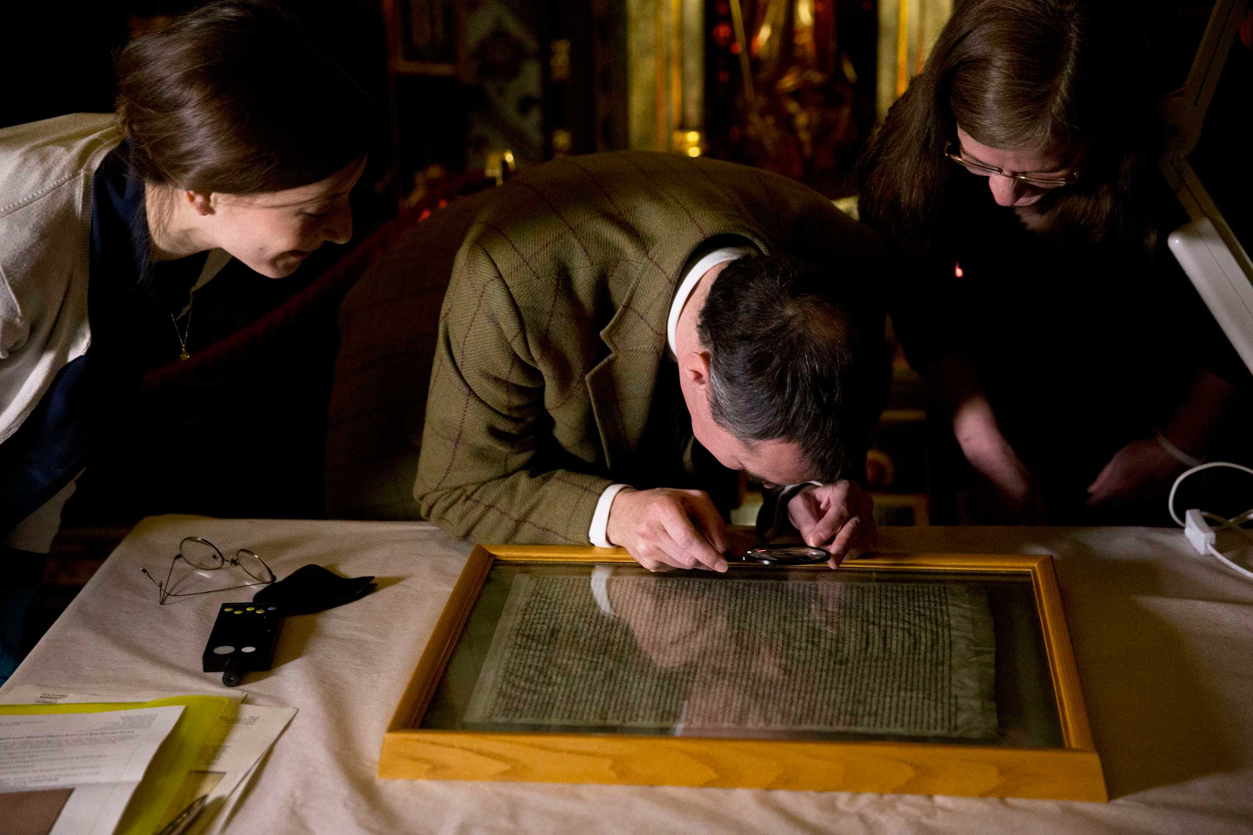 The Salisbury Cathedral copy of the Magna Carta is viewed by archivists before being displayed alongside the other three surviving original parchment engrossments of the Magna Carta, as they are displayed to mark the 800th anniversary of the sealing of the Magna Carta in 1215, in the Queen's Robing Room at the Houses of Parliament in London on Feb. 5, 2015.