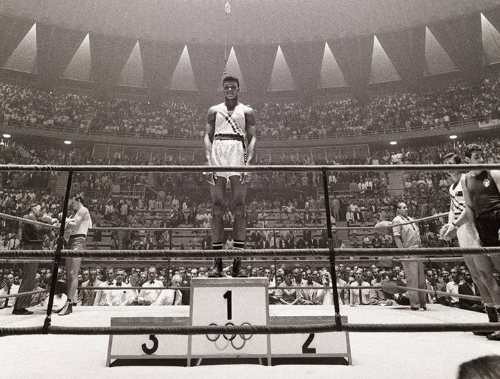 Ali at the Summer Olympics in Rome, 1960                                                              Marvin E. Newman:   I was photographing the 1960 Olympics in Rome for Sports Illustrated. I was assigned to cover boxing the night Cassius Clay was fighting for the heavyweight gold medal. I was stationed at press ringside, listening to the boxing writers complaining that Clay wasn't landing any punches. I was watching the same fight and saw the machine-gun rapidity of his blows destroying his opponent. During his early years, Ali continued to be underestimated by the press, but that night he took home the gold medal for the United States.  Marvin E. Newman is a contributing photographer for Sports Illustrated and previously was for LIFE magazine.