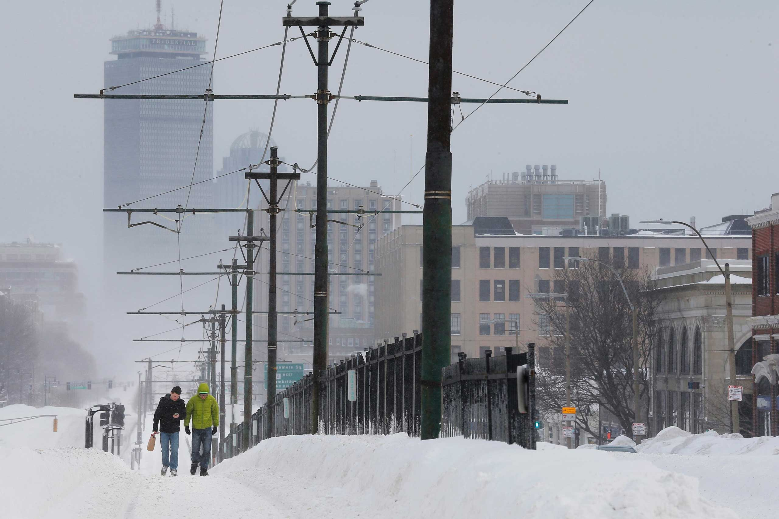 Pedestrians walk along snow covered, MBTA subway rails on Commonwealth Avenue in Boston, Massachusetts following a winter storm on Feb. 15, 2015.
