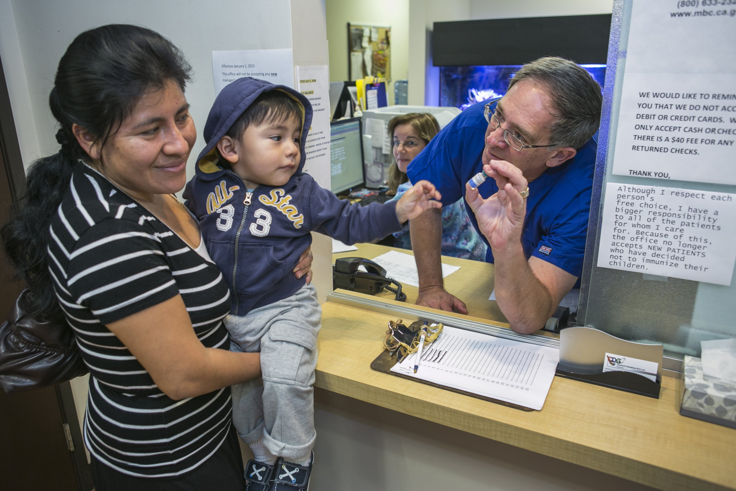 Pediatrician Dr. Charles Goodman talks with Carmen Lopez, who is holding her 18-month-old son Daniel after being vaccinated with the measles-mumps-rubella (MMR) vaccine, at his practice in Northridge, Calif., on Jan. 29, 2015