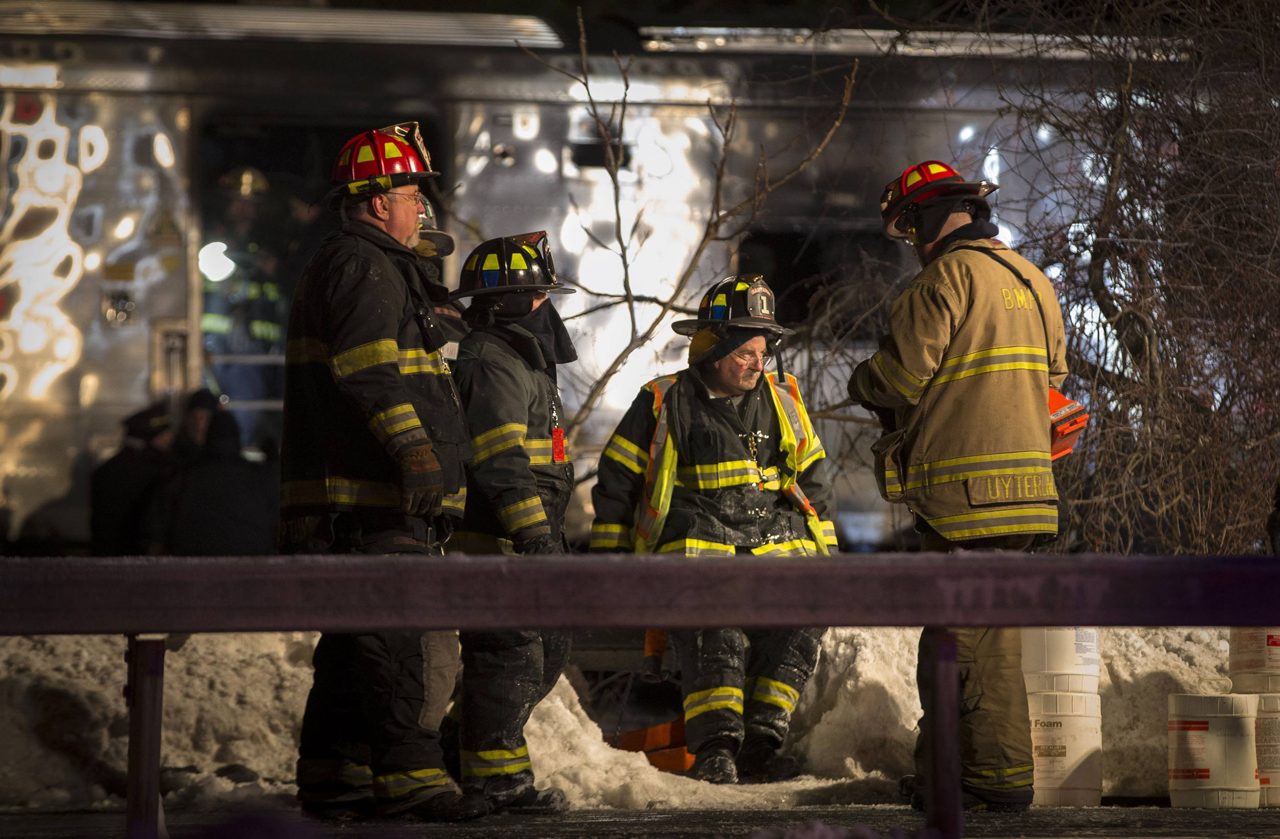 Firefighters and Emergency workers stand near a burnt Metro North commuter train car near the town of Valhalla, N.Y. on Feb. 3, 2015.