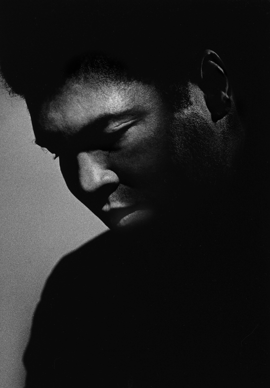 Ali in New York City, 1984                               Michael Tighe:  I shot this photo in 1984 when the world was just starting to learn about his affliction with Parkinson's syndrome. I had shot him 10 years earlier when he was the champ, so it was very difficult seeing him like this, our hero. I shot him a third time in 1999 for Athlete of the Century at his farm in Indiana. When the shoot was over, my assistants and I were invited to have lunch with him and his family at their house. I brought a print of this photo, which I presented to him after lunch. He had never seen it. I handed it to him. He stared at it quietly for a long beat. His eyes watered up, and he handed it back. Everyone got very quiet and uneasy. Then he gestured with the most beautiful smile for me to sign it for him. I got teary-eyed. It is the most cherished moment of my photographer's life.  Michael Tighe is a portrait photographer.