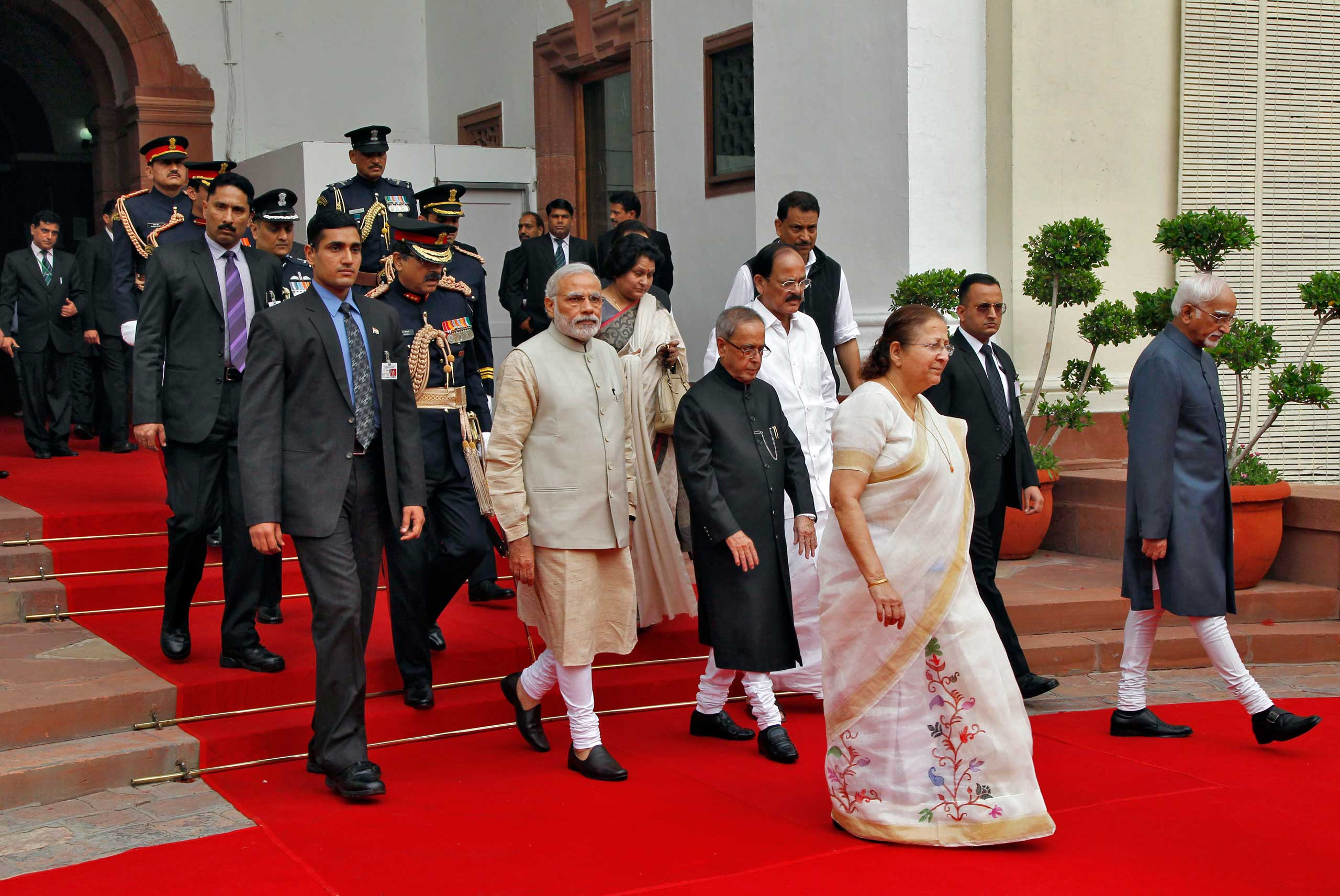India's Prime Minister Narendra Modi, center left, and members of his government walk inside the parliament premises as they arrive to attend the first day of the budget session in New Delhi, Feb. 23, 2015.