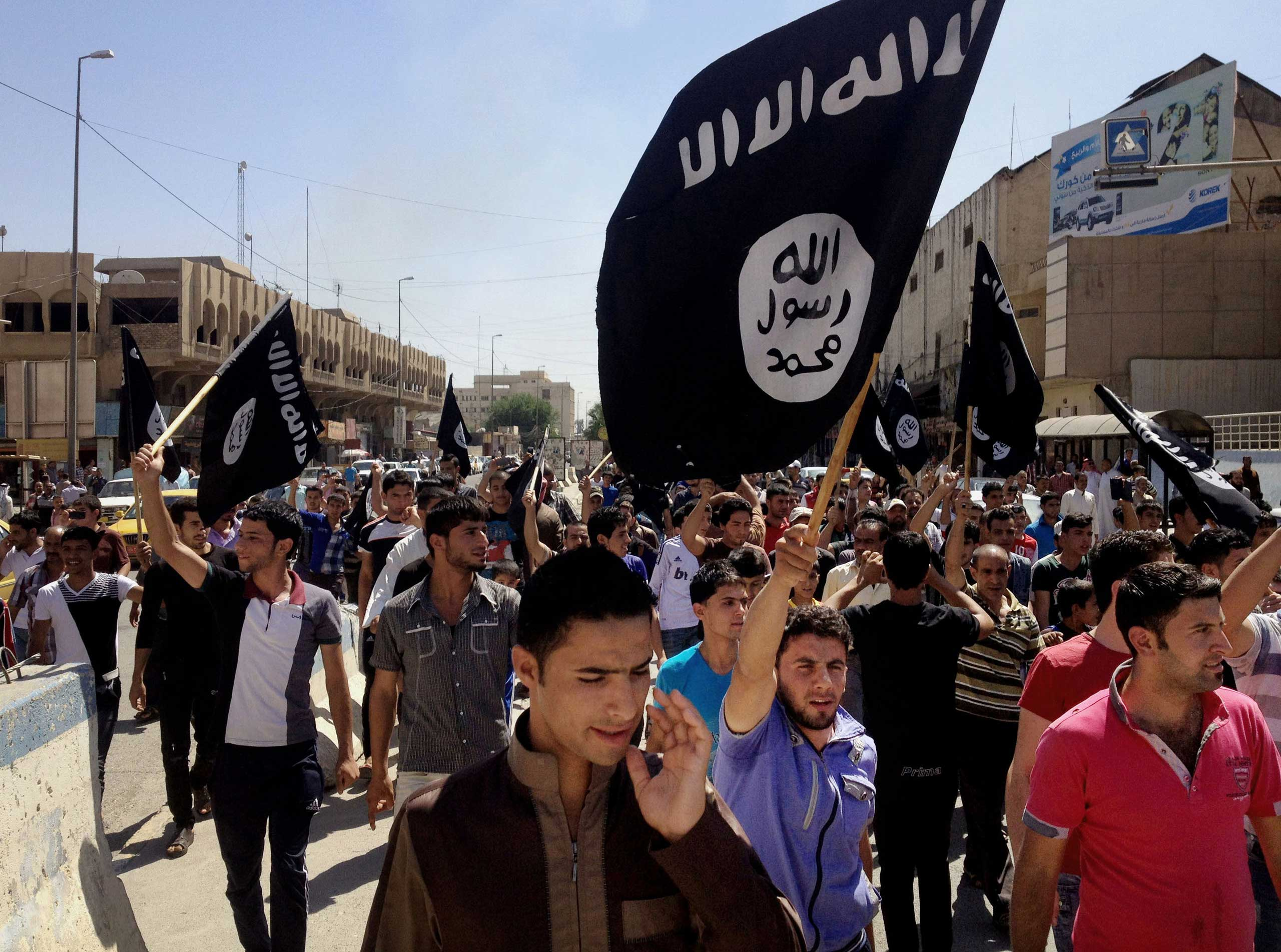 Demonstrators chant ISIS slogans as they wave the group's flags in front of the provincial government headquarters in Mosul, June 2014.