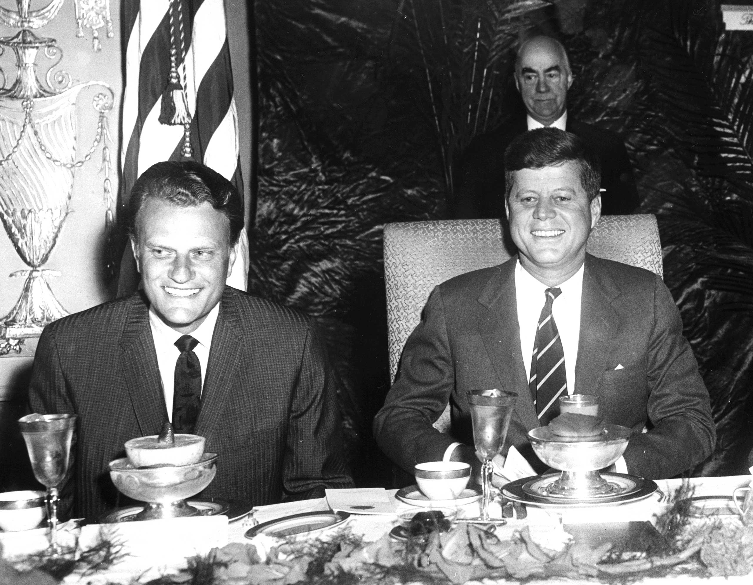John F. Kennedy, the nation's first Catholic president, eats breakfast with Southern Baptist minister Billy Graham at the National Prayer Breakfast in 1961.