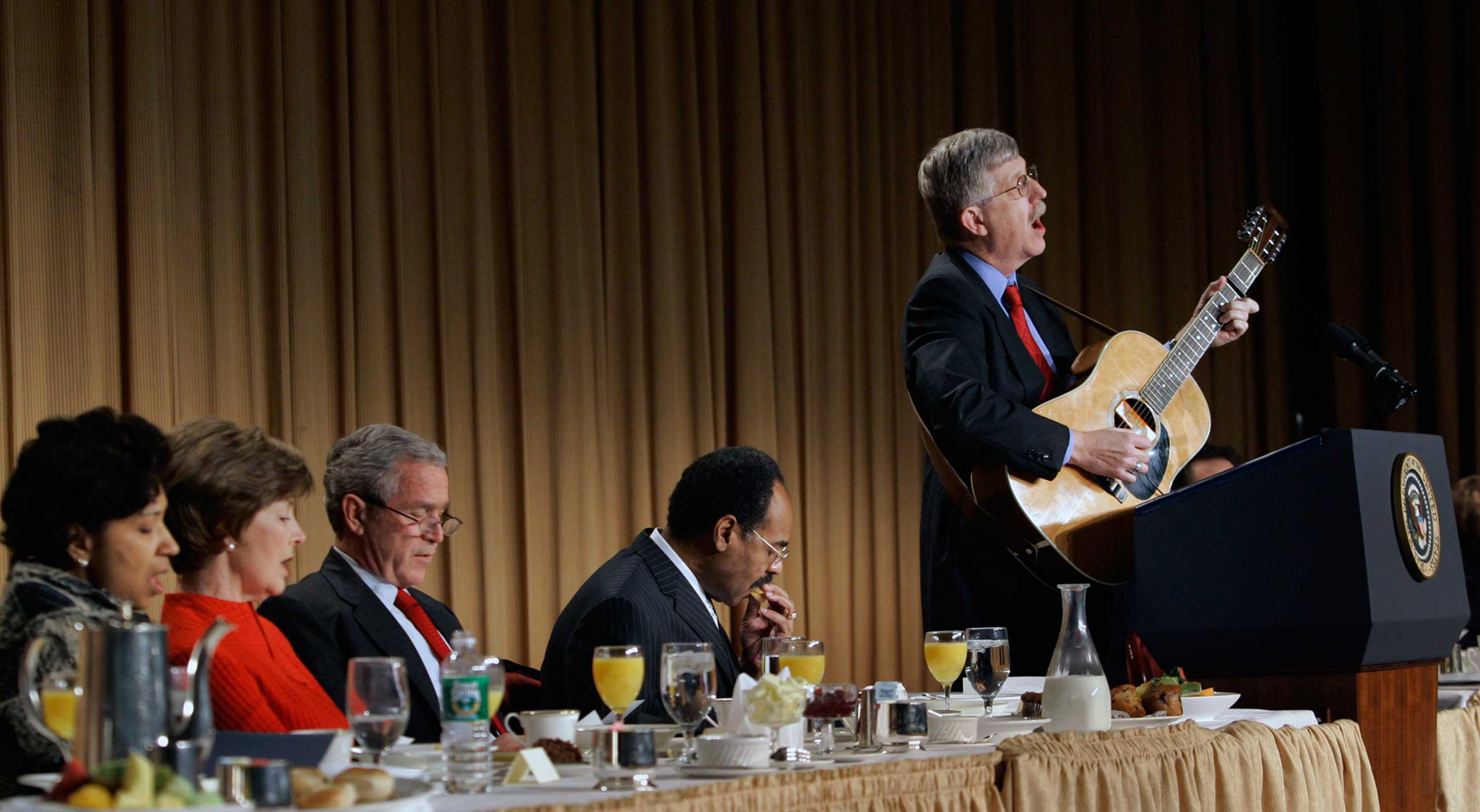 Dr. Francis Collins, head of the Human Genome Project, sings and plays guitar at the 2007 National Prayer Breakfast while President George W. Bush and Democratic Rep. Emanuel Cleaver II watch.