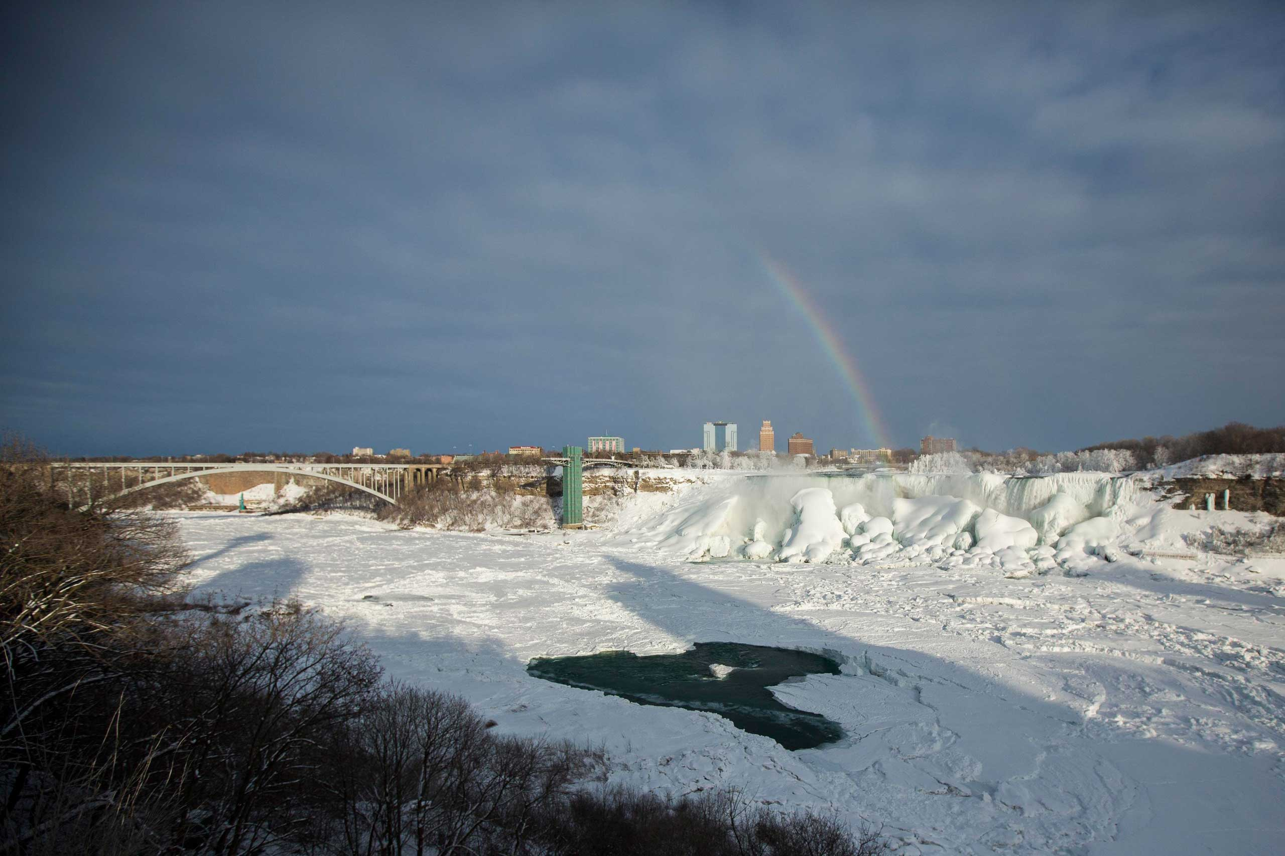 A rainbow appears over the partially frozen American Falls in sub freezing temperatures in Niagara Falls, Ontario, Canada, Feb. 17, 2015.