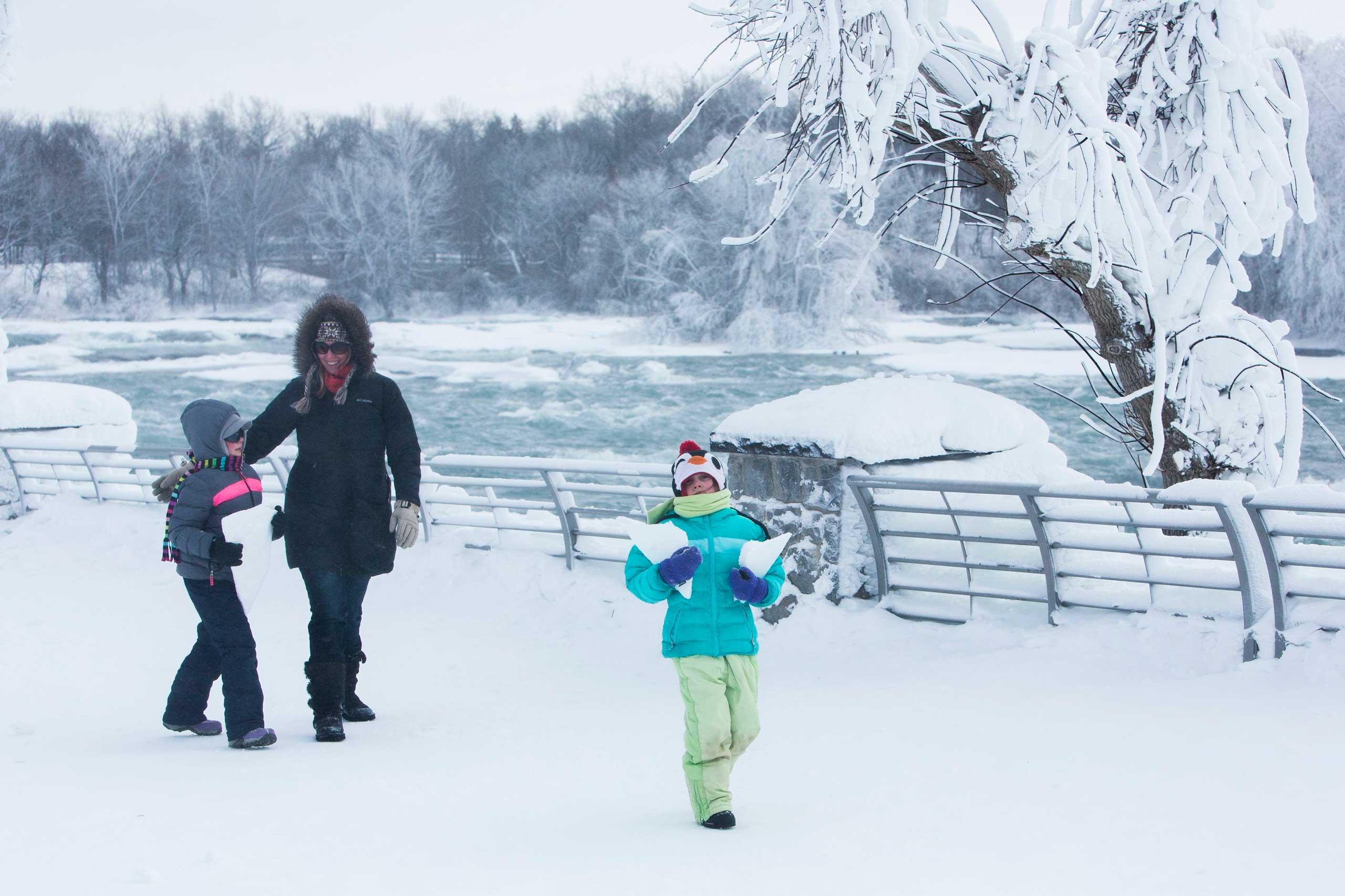 A family walks through the snow near the frozen Niagara Falls in Niagara Falls, N.Y.,Feb. 17, 2015.