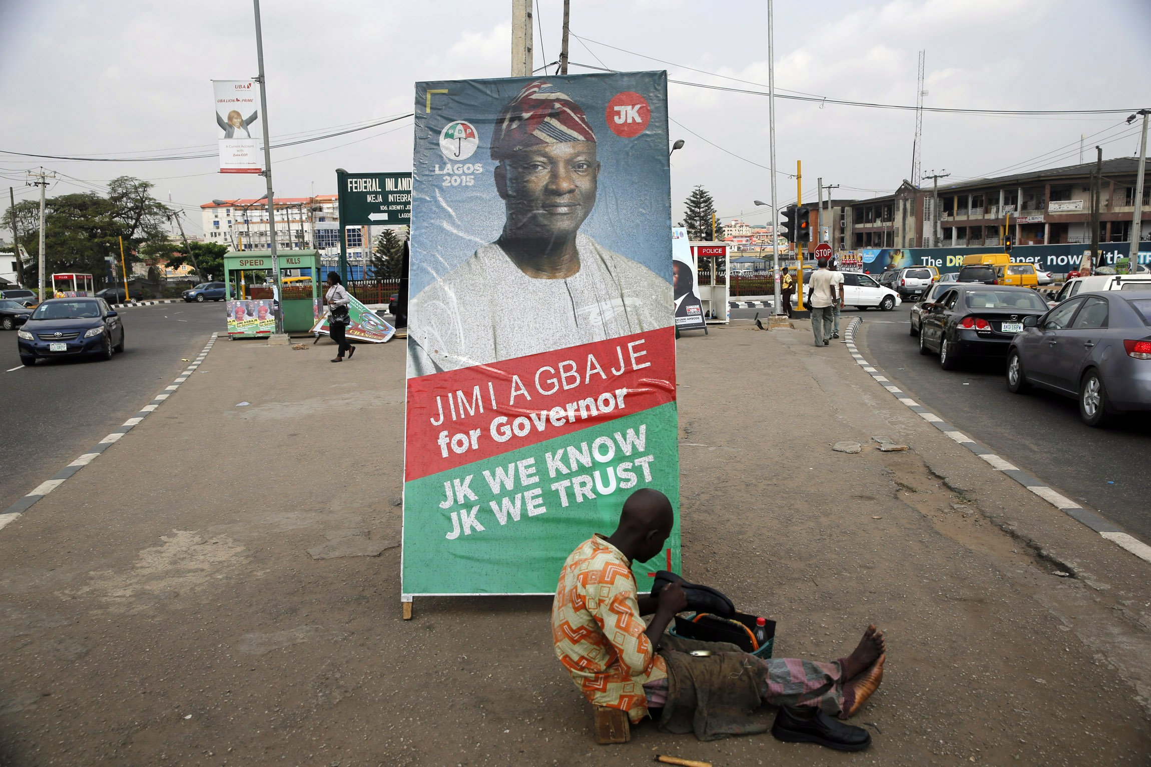 A shoe-mender works near a poster campaigning for frontline contender and Lagos governorship candidate for the People's Democratic Party (PDP) Jimi Agbaje, along a road in the Ikeja district in Lagos, Nigeria on Feb. 3, 2015.