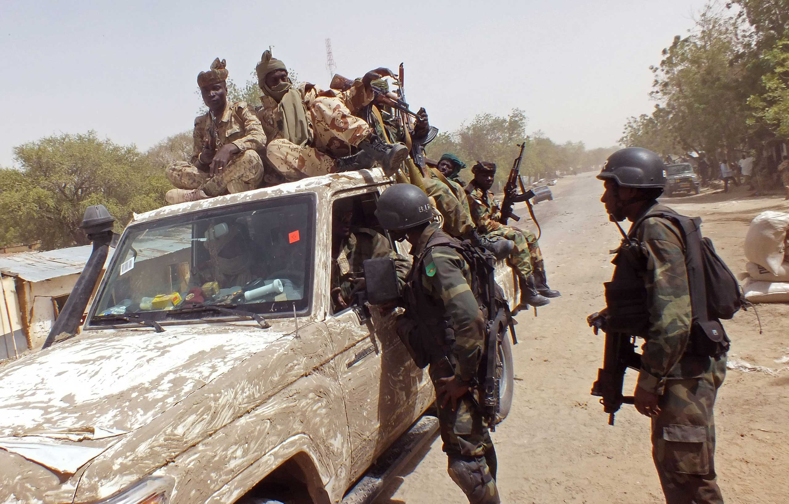 Chadian soldiers on top of a truck, left,  speak to Cameroon soldiers, right, standing next to the truck, on the border between Cameroon and Nigeria as they form part of the force to combat regional Islamic extremists force's including Boko Haram, near the town of  Gambarou, Nigeria, Feb. 19, 2015.