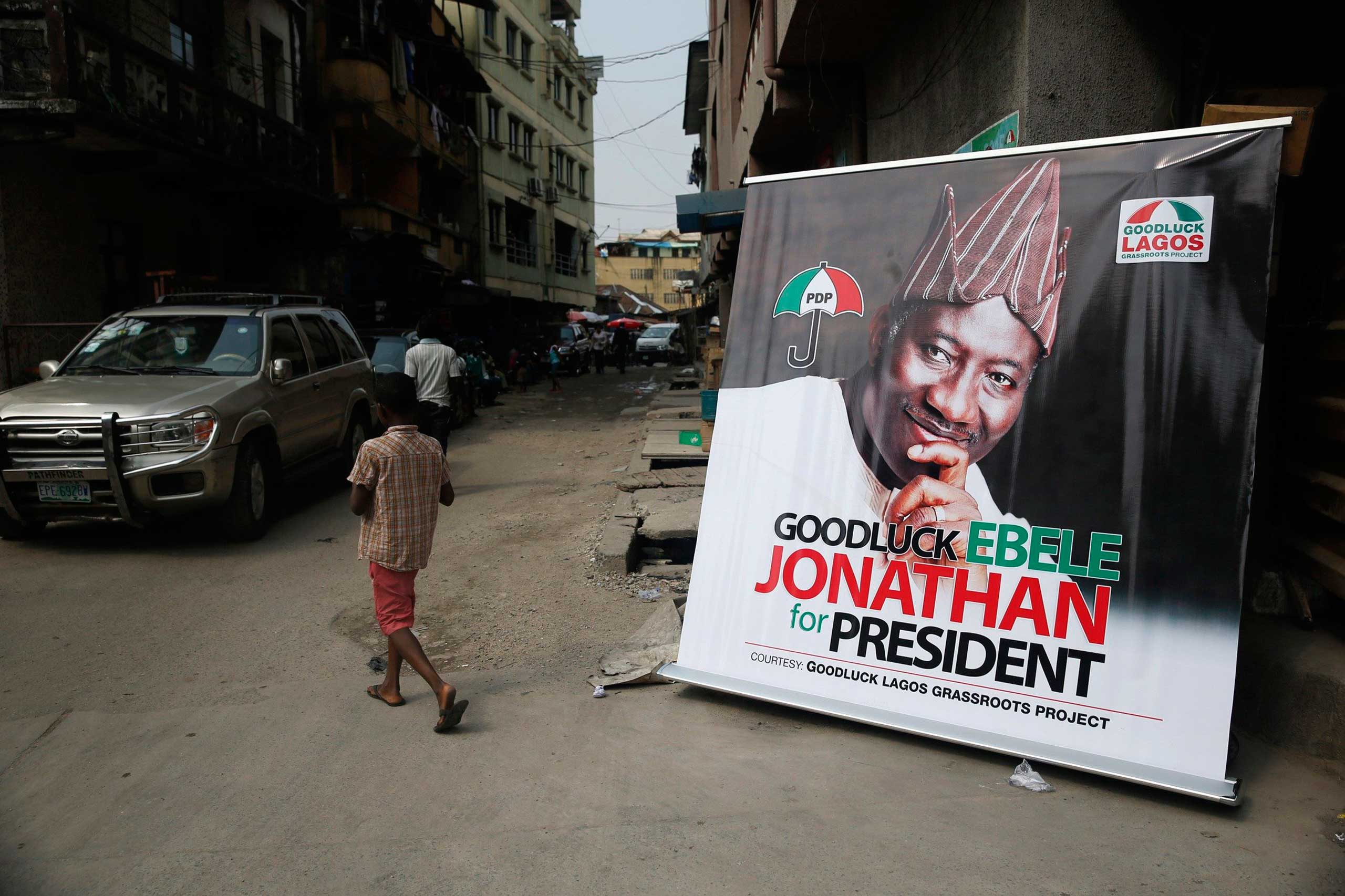 A boy walks near a banner campaigning for Nigeria's President Goodluck Jonathan along a street at Campus Square neighborhood in Lagos, Feb. 2, 2015.