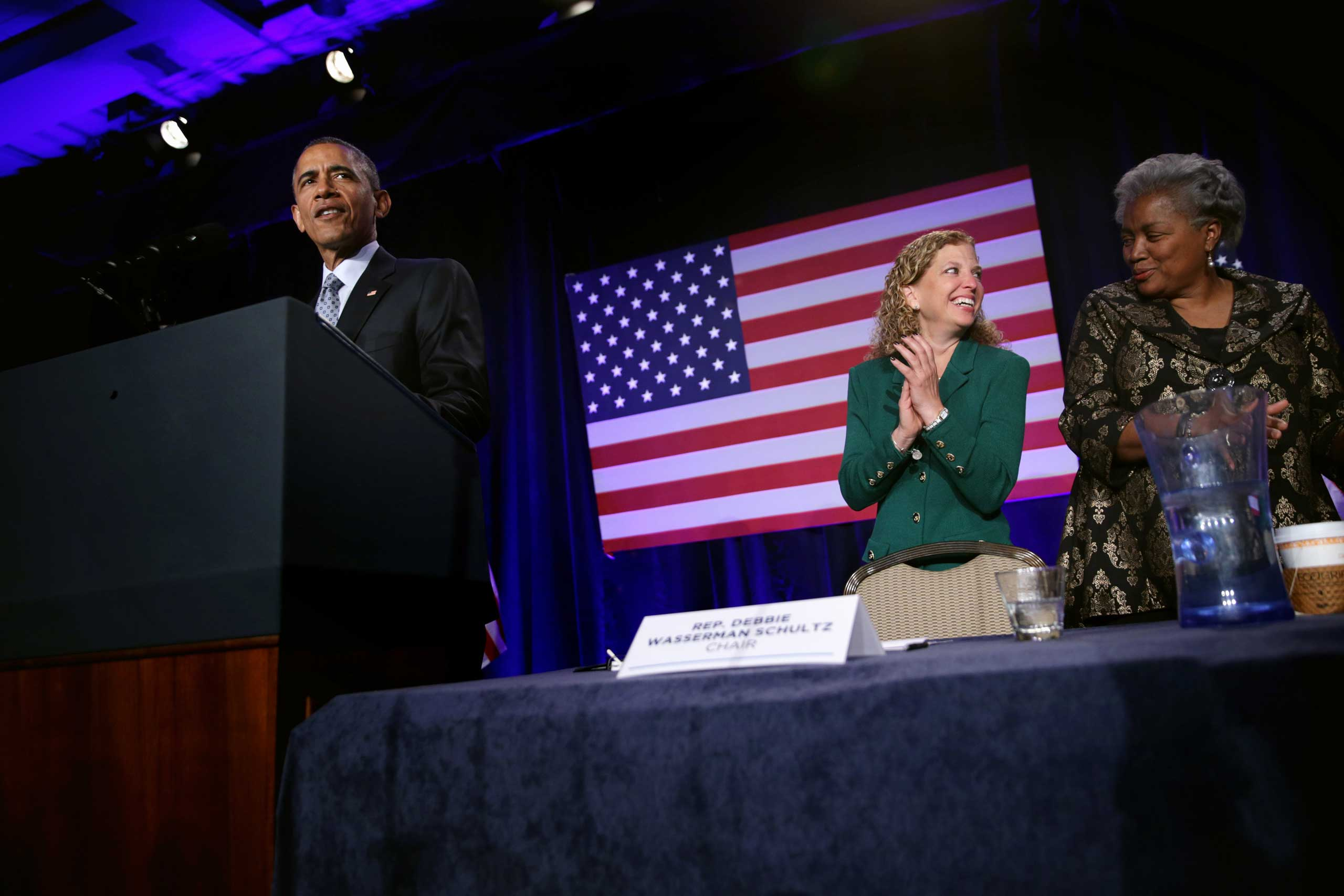 President Obama speaks as Democratic National Committee Chair and Rep. Debbie Wasserman Schultz and Vice Chair for Voter Registration and Participation Donna Brazile share a moment during the General Session of the 2015 DNC Winter Meeting, Feb. 20, 2015 in Washington, DC.
