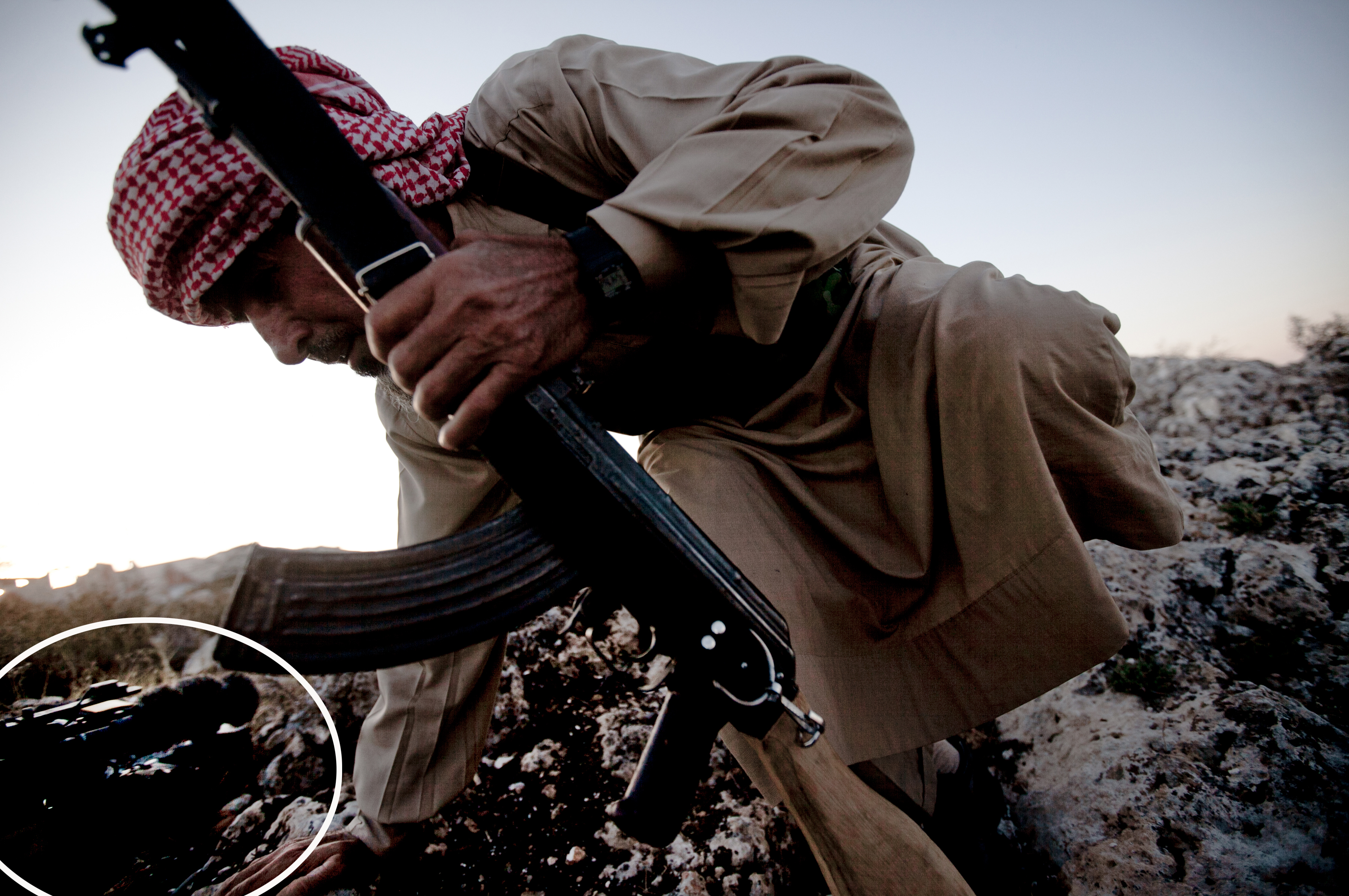 """A Syrian opposition fighter takes cover during an exchange of fire with government forces in Telata village, Syria on Sept. 29, 2013. This <a href=""""http://www.ap.org/Content/AP-In-The-News/2014/AP-severs-ties-with-photographer-who-altered-work"""" target=""""_blank"""">original</a> photo shows a journalist's video camera on the ground in the left corner of the frame, which was later removed by the photographer."""