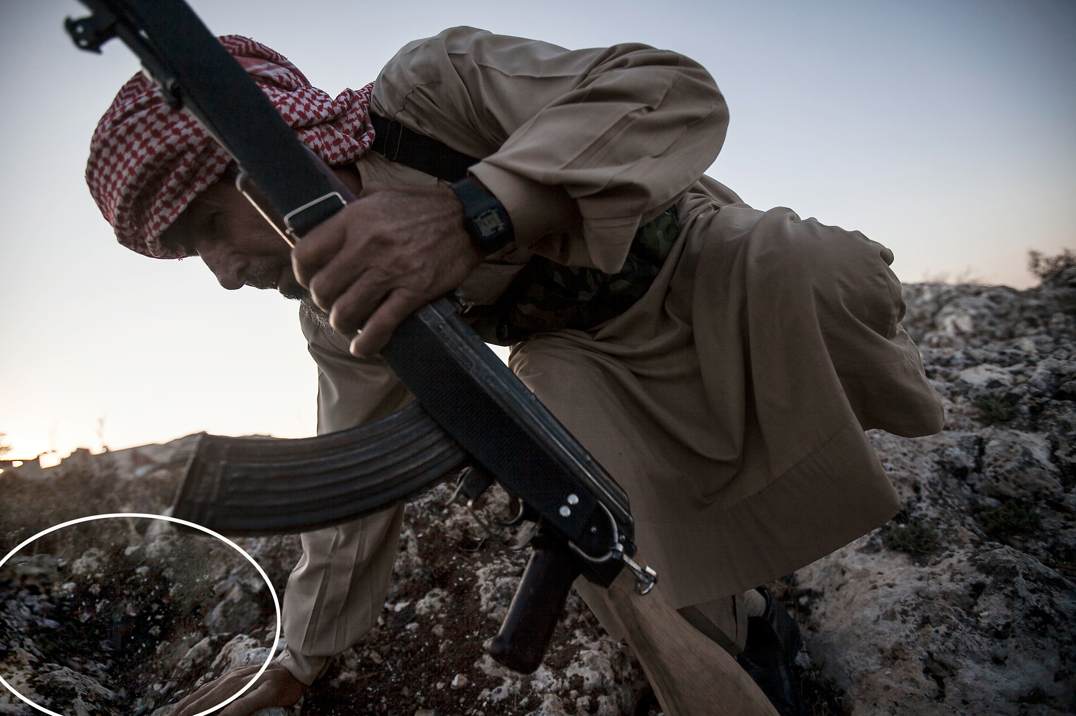 """A Syrian opposition fighter takes cover during an exchange of fire with government forces in Telata village, Syria on Sept. 29, 2013. This  <a href=""""http://www.ap.org/Content/AP-In-The-News/2014/AP-severs-ties-with-photographer-who-altered-work"""" target=""""_blank"""">manipulated</a>  photo was caught by the Associated Press which then severed ties with the freelance photographer, who it says violated its ethical standards by altering the photo."""
