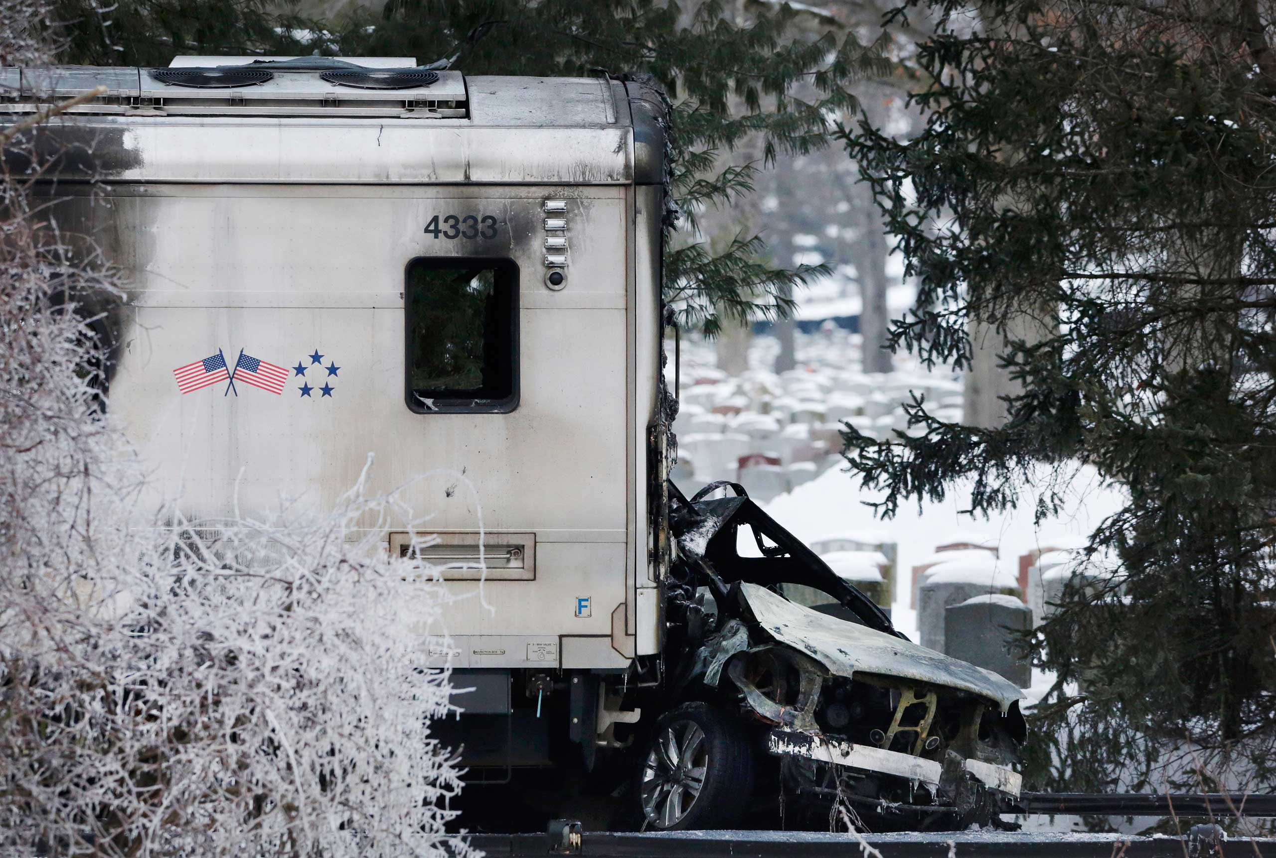 Feb. 4, 2015. A sports utility vehicle remains crushed and burned at the front of a Metro-North train, in Valhalla, N.Y. The commuter train slammed into the SUV stuck on the tracks, killing the driver and five train passengers.