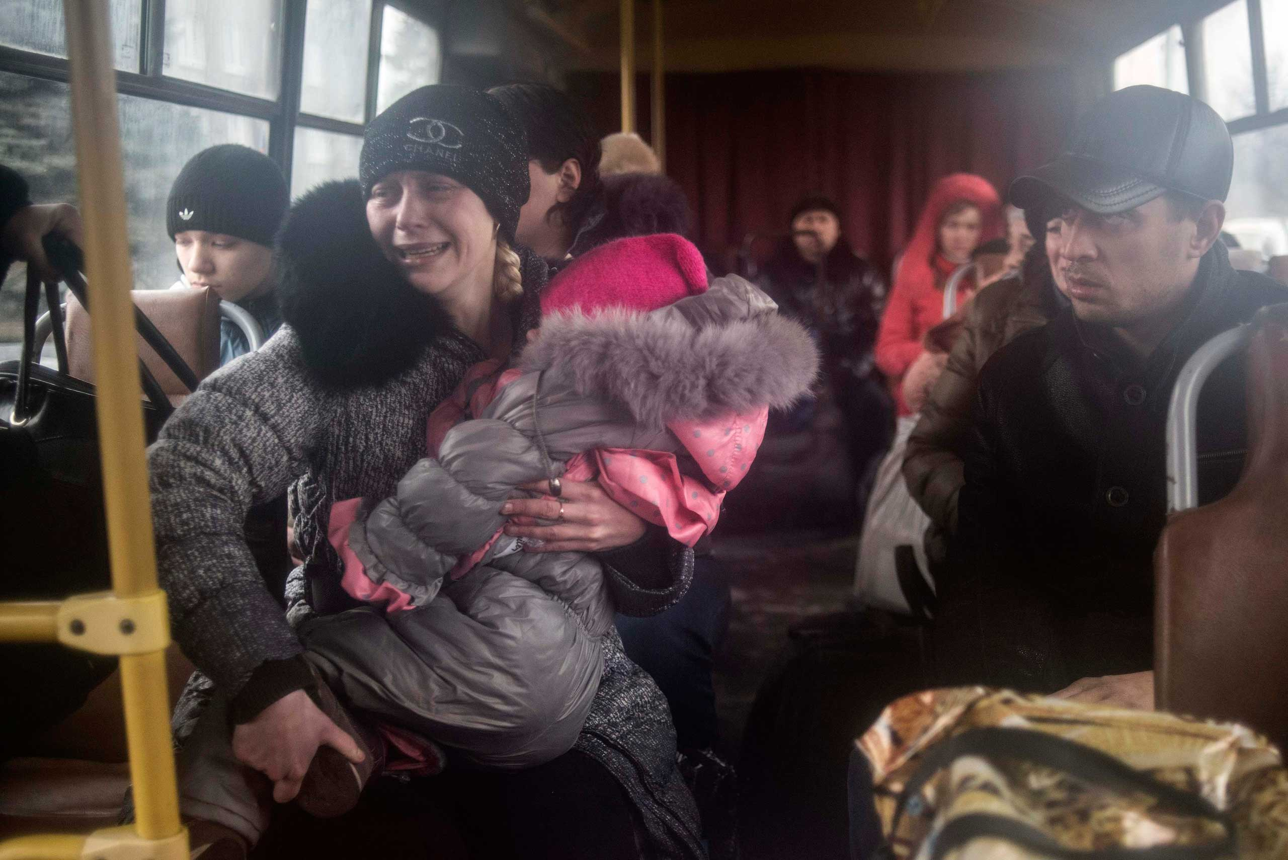 Feb. 3, 2015. People sit inside a bus before the departure, as they flee due to the military conflict in the town of Debaltseve, Ukraine. Fighting has been particularly intense around the town, a major rail and road junction northeast of the city of Donetsk, which government troops are still holding.