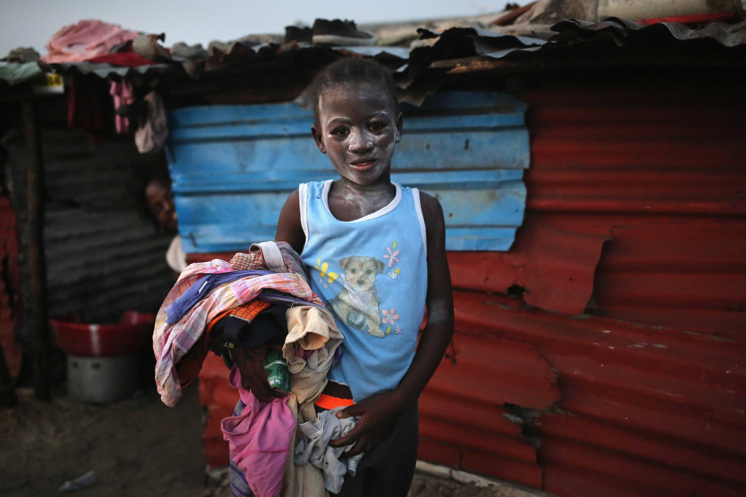 Jan. 31, 2015. A girl collects her family's laundry after drying it on a rooftop in the West Point township in Monrovia, Liberia. Life has slowly begun to return to normal for many Liberians, as the government says there are currently fewer than 10 cases of Ebola in the country.
