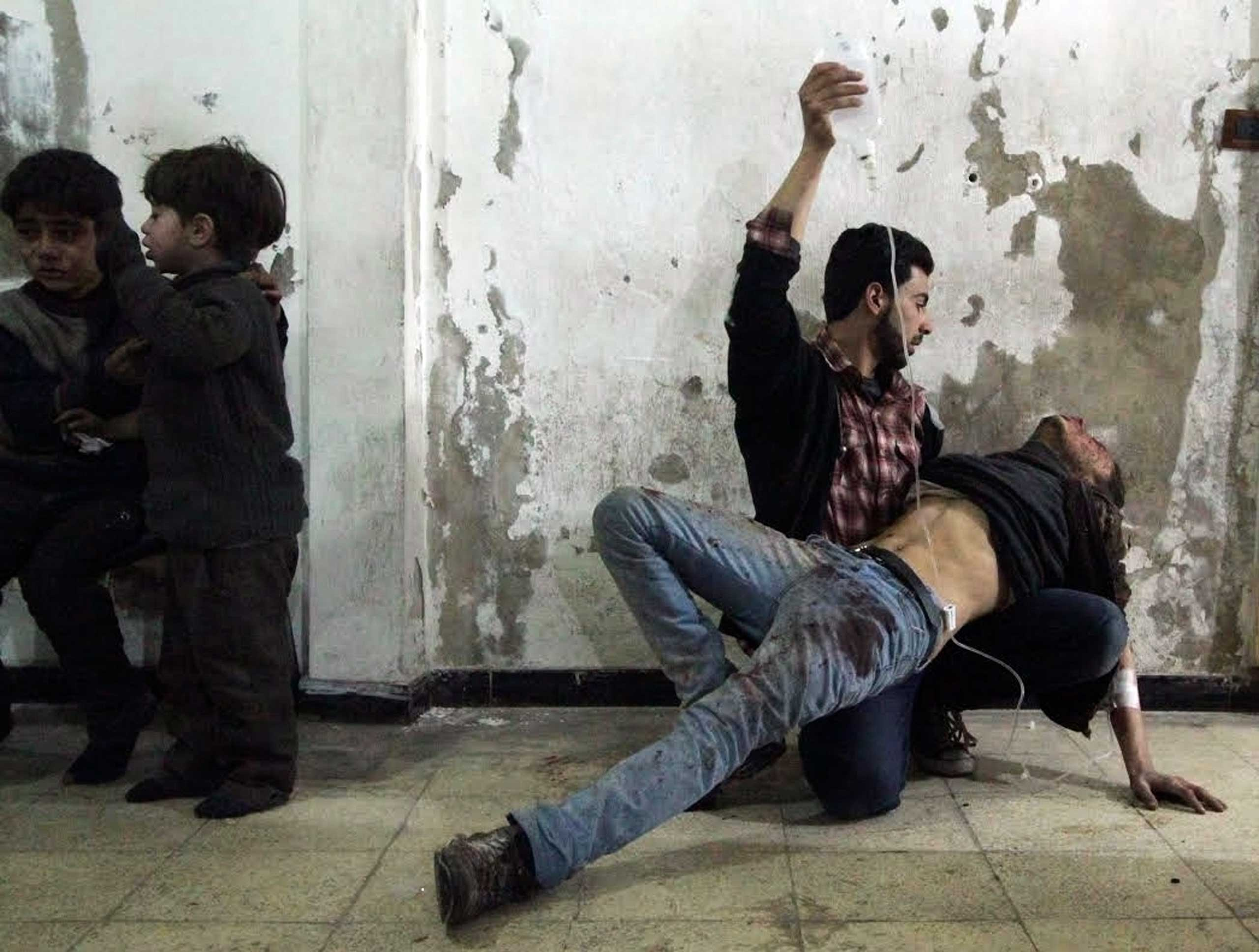 Feb. 2, 2015. A man gives medical assistance to an injured man as two wounded children wait nearby at a field hospital after what activists said was an air strike by forces of Syria's President Bashar al-Assad in the Duma neighbourhood of Damascus.