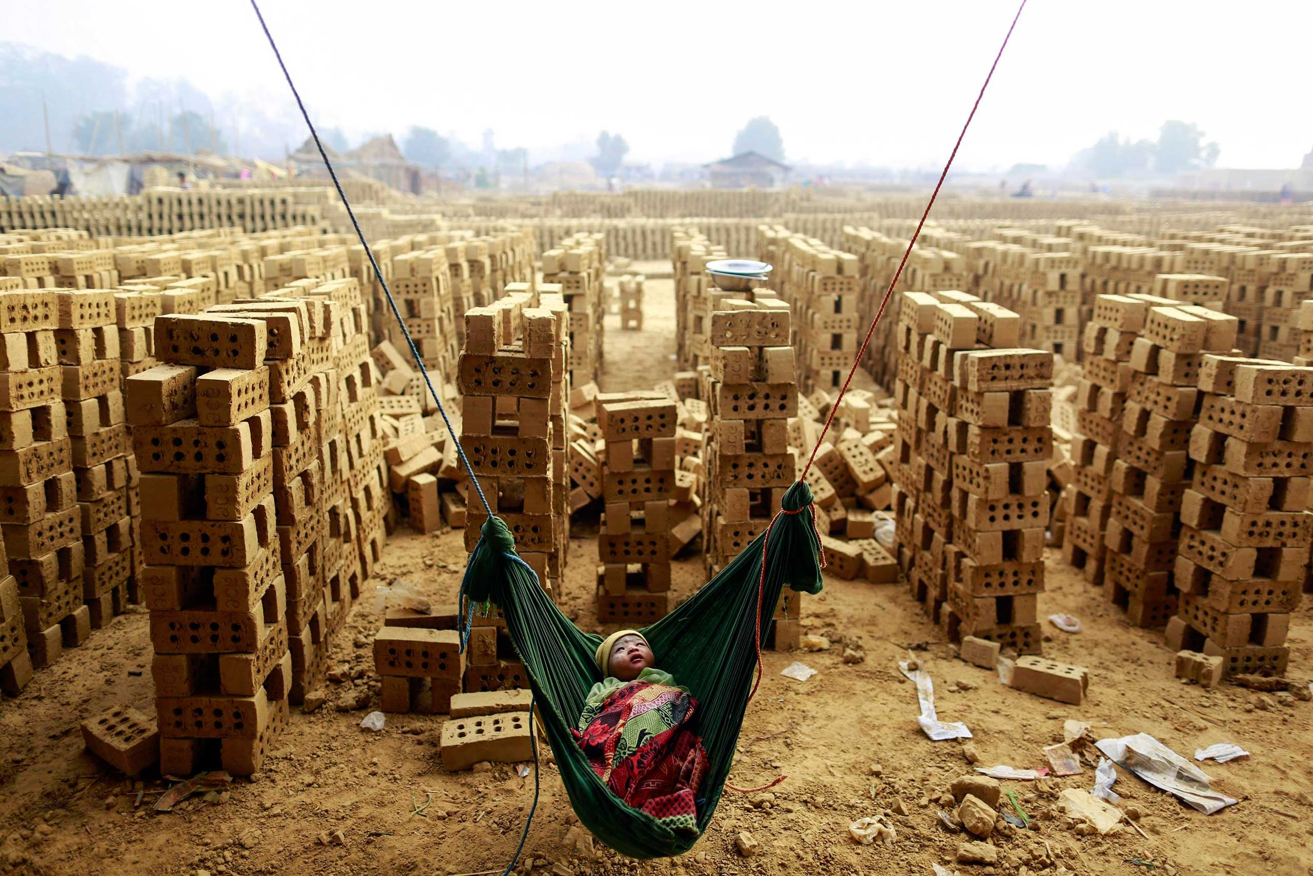 Feb. 1, 2015. A boy sleeps in a hammock while his mother works at a brick kiln on the outskirts of Yangon, Myanmar.