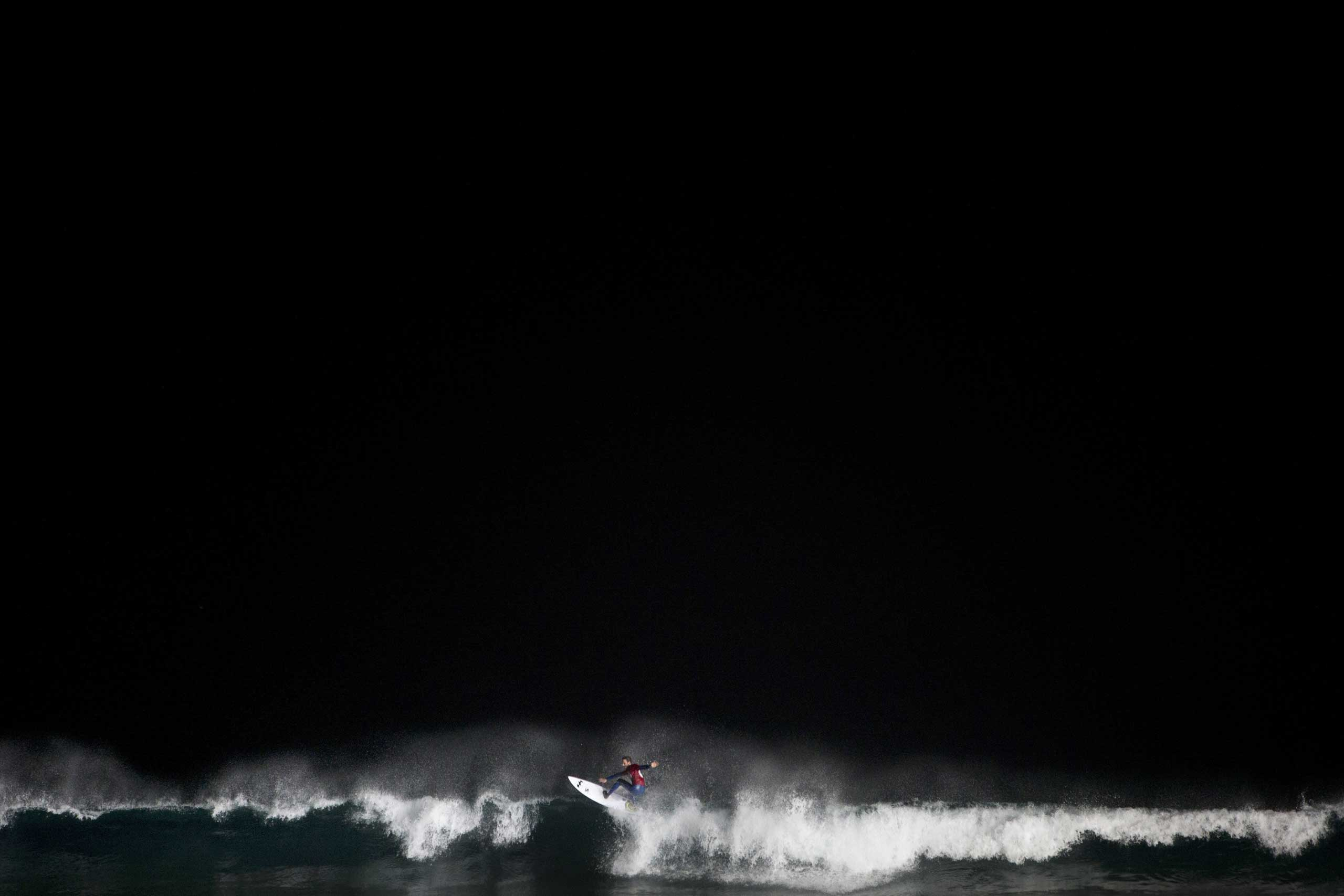 Feb. 4, 2015. An Israeli surfer catches a wave during a night surfing competition in the Mediterranean sea in Ashdod, southern Israel. About 40 surfers participated in the competition.
