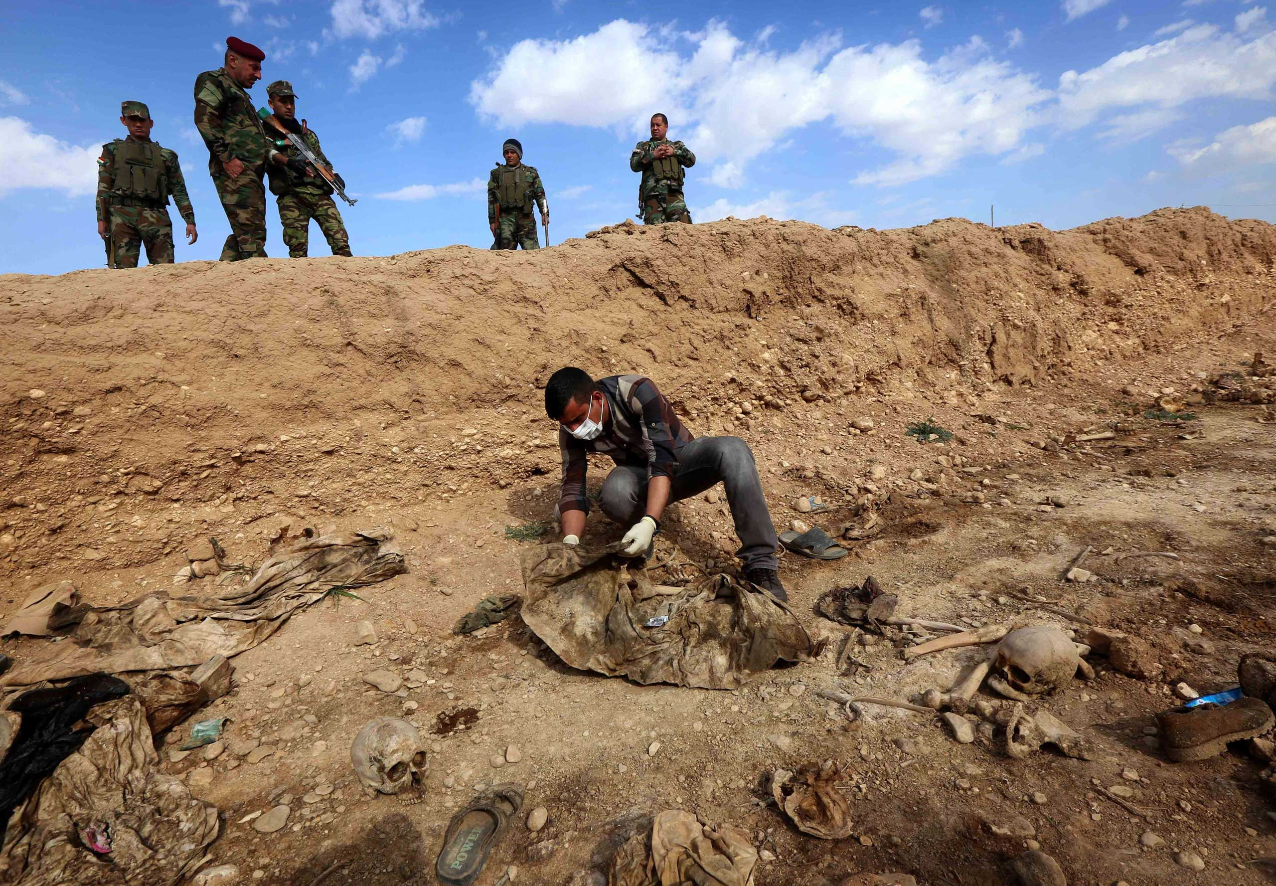 Feb. 3, 2015. An Iraqi man inspects the remains of members of the Yazidi minority killed by ISIS jihadist group after Kurdish forces discovered a mass grave near the village of Sinuni, in the northwestern Sinjar area. The grave, containing the remains of about 25 people, was found during a search for explosives that ISIS often leaves behind, posing a threat to security forces and civilians even after they withdraw.