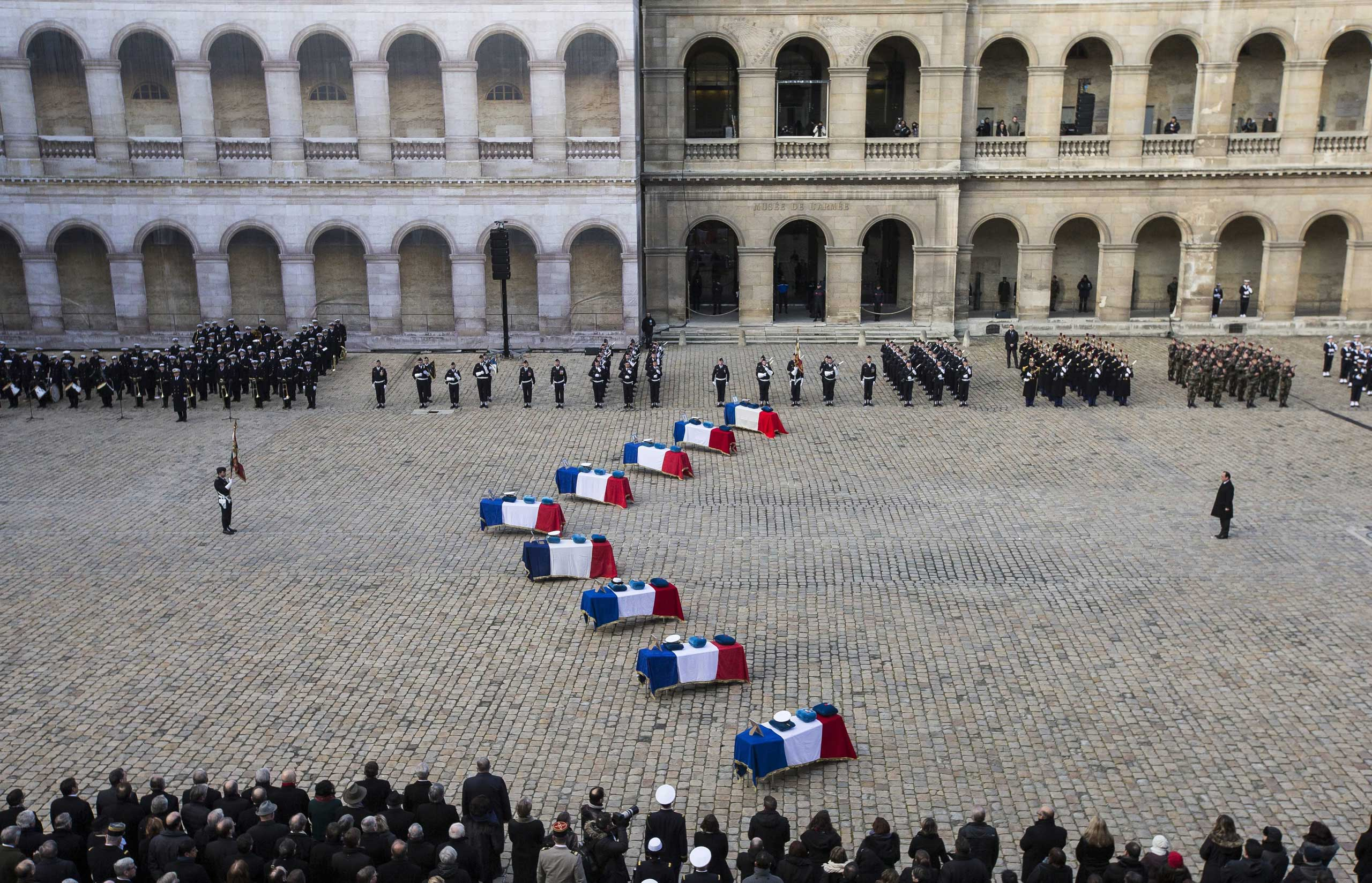 Feb. 3, 2015. French President Francois Hollande (R) stands in front of the coffins of the nine French officers killed in Spain, in the courtyard of the Invalides in Paris. The officers died when a Greek two-seater F16 fighter jet crashed during a NATO training exercise  inside Los Llanos air base, in Albacete, central Spain. The death toll has risen to 11 and 20 soldiers were also injured.