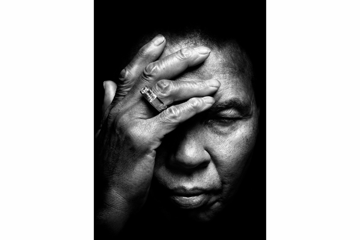 Ali in Paradise Valley, Ariz., 2009                                                              Platon:  I never thought I would get to meet and photograph Muhammad Ali. I remember feeling overwhelmed as I rang the doorbell. Looking down, there was a giant doormat, with a capital letter A woven into the fabric. It occurred to me that there were two things that make Ali 'the Greatest' — perhaps the greatest man that ever lived. Firstly, his physical power, beauty, speed and agility, and secondly, his unique skills as an orator. Sadly, as I stepped over the letter A, I realized that Parkinson's disease had robbed the man of these two strengths. How in the world could I take a portrait of Muhammad Ali that is a fitting tribute to his contribution to the 20th century? As he silently shuffled into the room, my path became clear. Though robbed of his physical armor, he revealed to me that most important thing of all: his spirit and strength of character. It was, after all, his heart that informed his political, competitive and spiritual quests. In this picture, I focus entirely on Muhammad Ali the human being. Here there is no playacting or gimmicks. As the modernists always said, less is more. As his eyes closed, his hand gently rose to caress his brow. No one ever thought that Muhammad Ali could be so tender and sensitive. As we finished the shoot, he was helped into his soft leather chair. His nurse switched on the TV — Muhammad loves to watch westerns and Elvis movies. A tray was placed on his lap, and a box of dominoes was opened — I was told it is his favorite pastime. I knelt by his feet, and together, we played dominoes for a few last minutes. As I made a cheeky connection with two dots on the domino pieces, his enlarged hand grabbed my shoulder, and he grunted a mischievous appreciation. I left his house feeling so honored that I had experienced a true connection with the legend, but more important, the man — Muhammad Ali.  Platon is a renowned portrait photogra