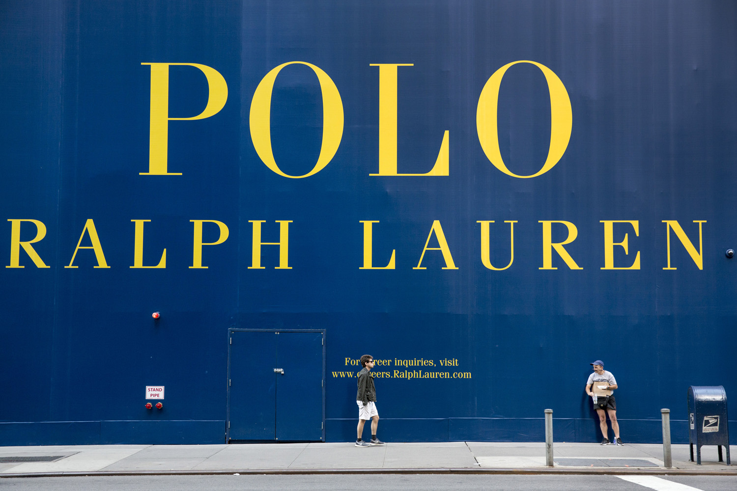 A man is seen next to a construction site of a new Ralph Lauren flagship store on Fifth Avenue, New York, June 21, 2014.