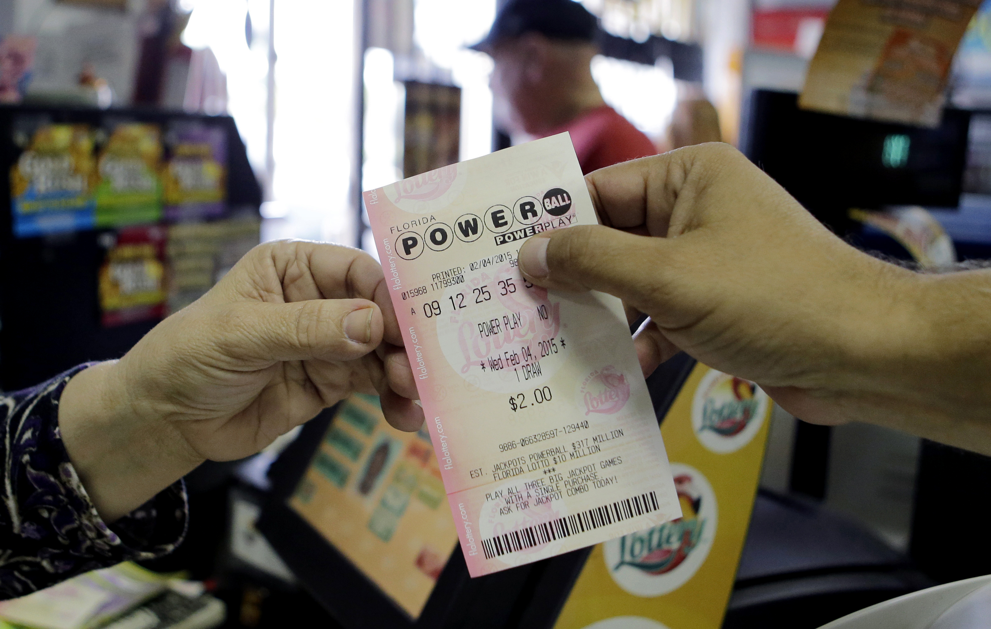 A store clerk hands a customer his Powerball ticket at a local grocery store in Hialeah, Fla., Wednesday, Feb. 4, 2015