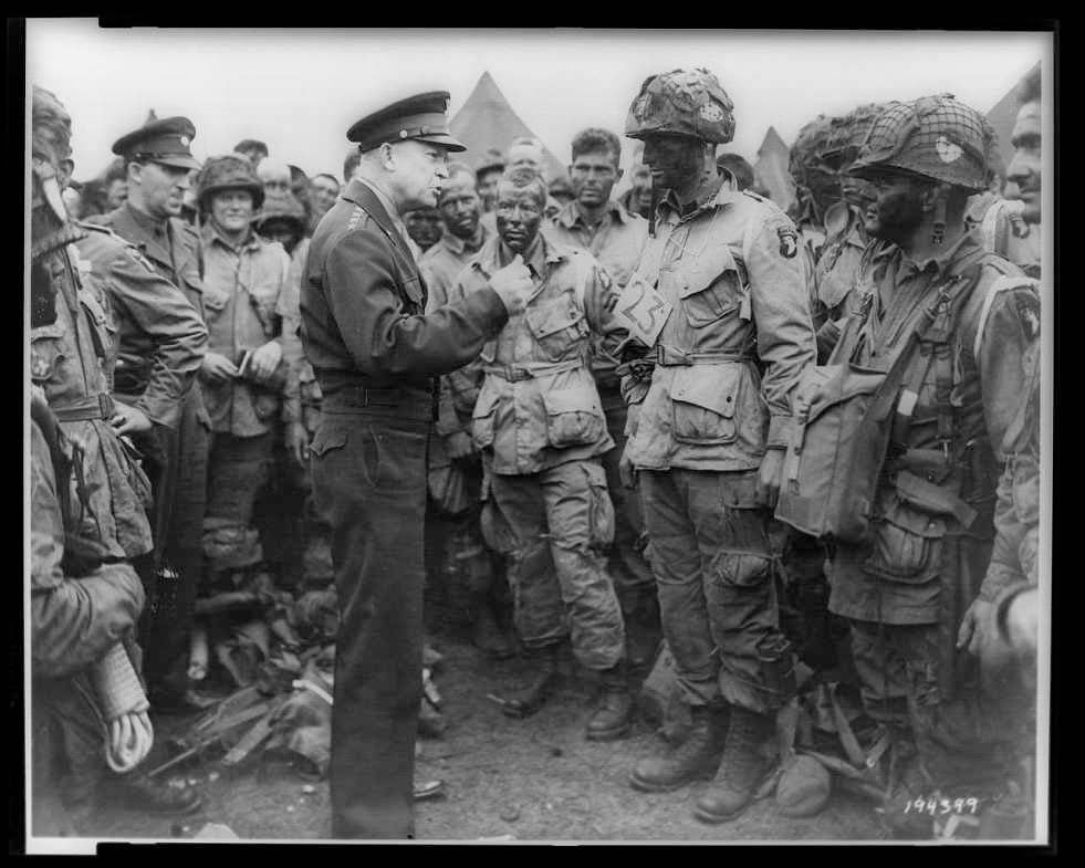 "June 5, 1944. General Dwight D. Eisenhower gives the order of the day, ""Full victory--nothing else"" to paratroopers somewhere in England, just before they board their airplanes to participate in the first assault in the invasion of the continent of Europe."