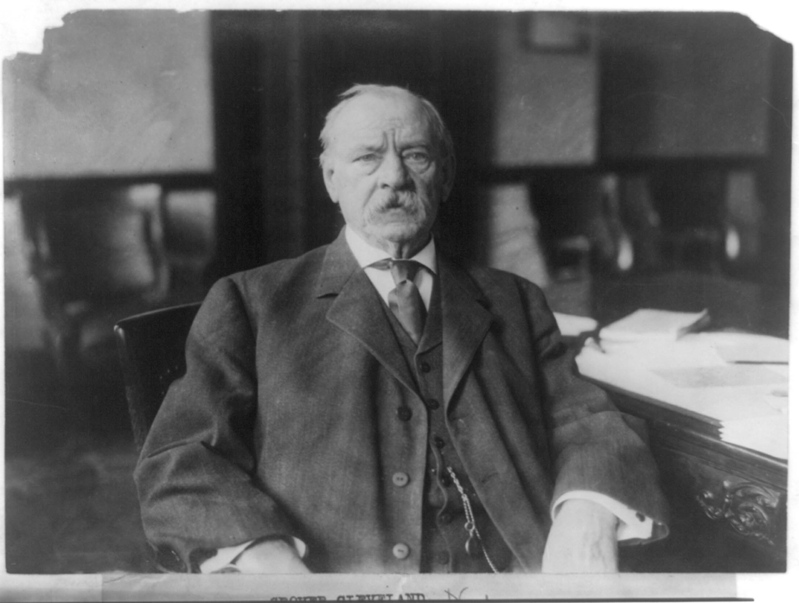 c. 1908. Grover Cleveland, half-length portrait, seated at desk.