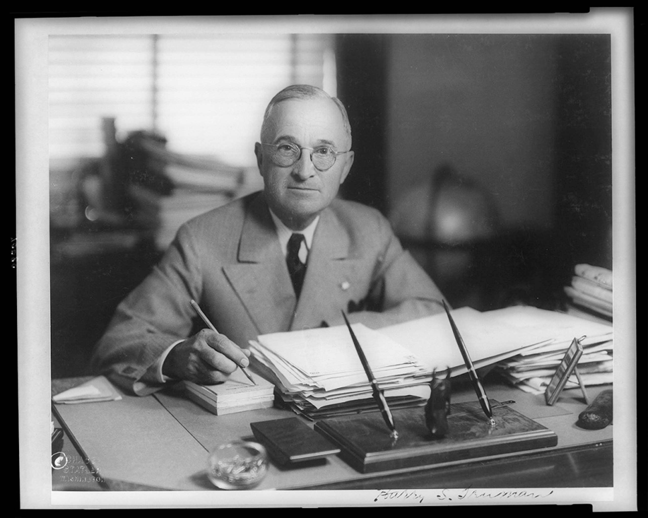 c. April 19, 1945. Harry Truman, half-length portrait, seated at desk, facing front, holding pencil.