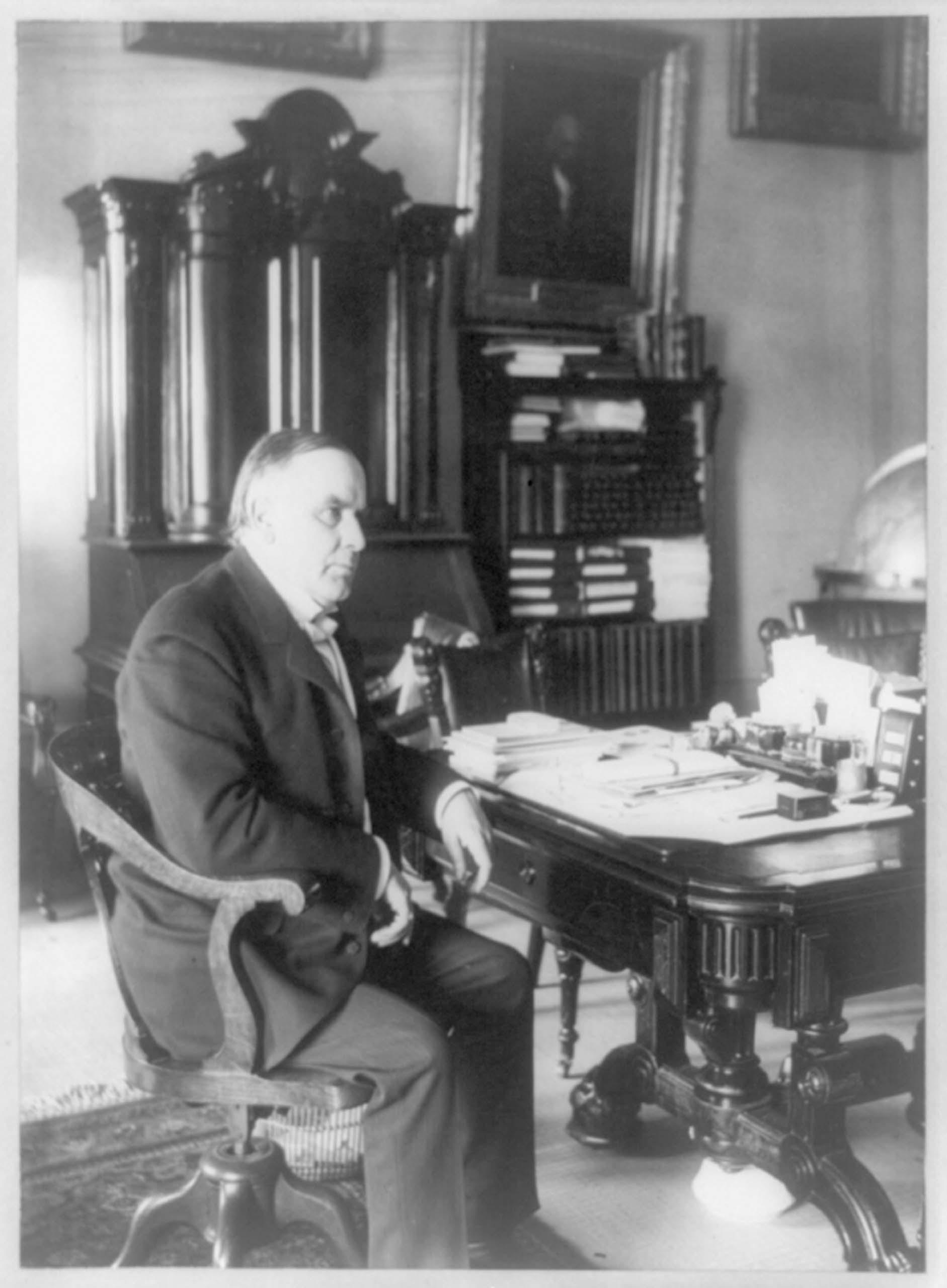 c. June 7, 1898. William McKinley, full length portrait, seated at desk, facing right.