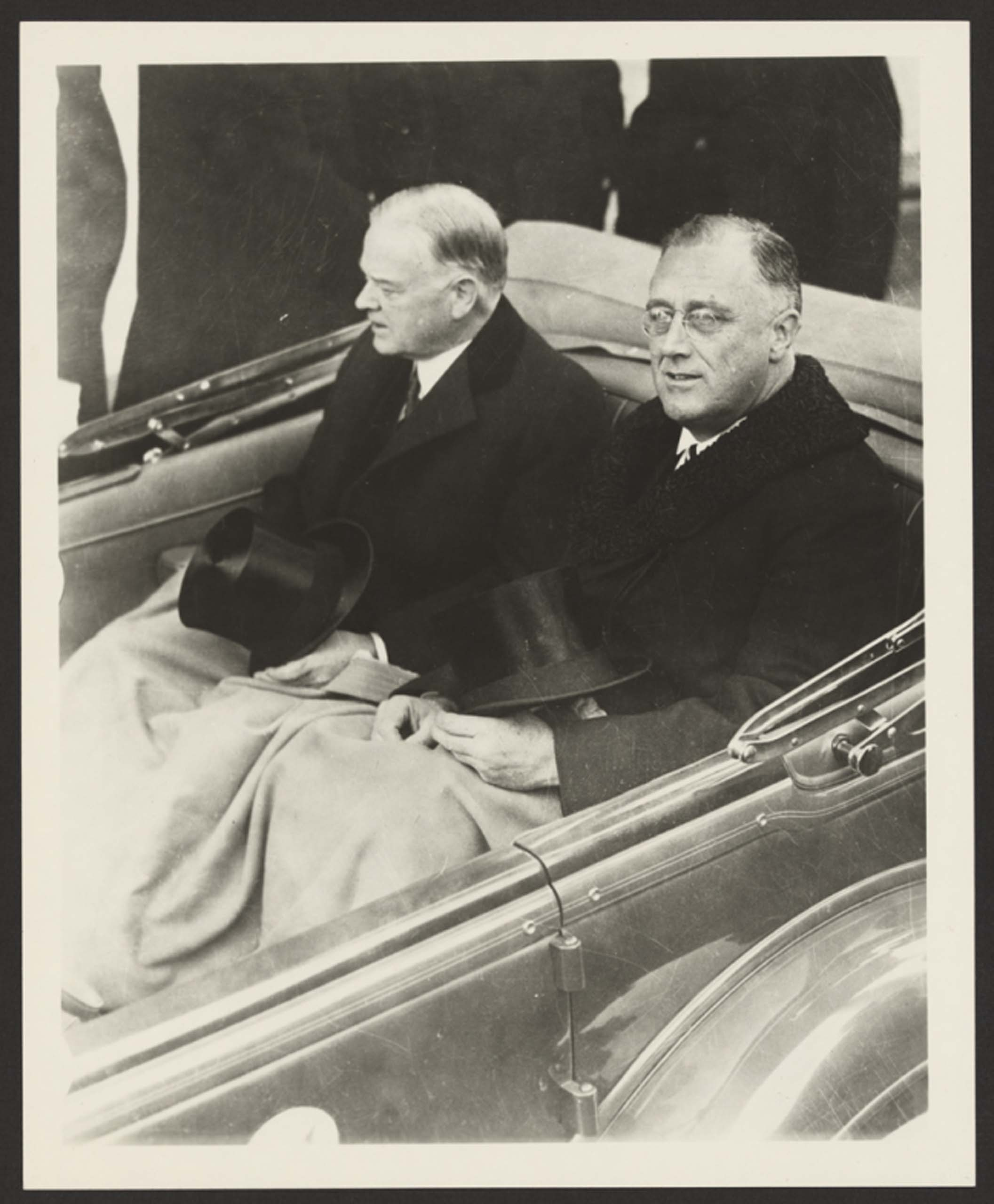 March 4, 1933. Franklin Delano Roosevelt and Herbert Hoover in a convertible automobile on their way to the U.S. Capitol for Roosevelt's inauguration.