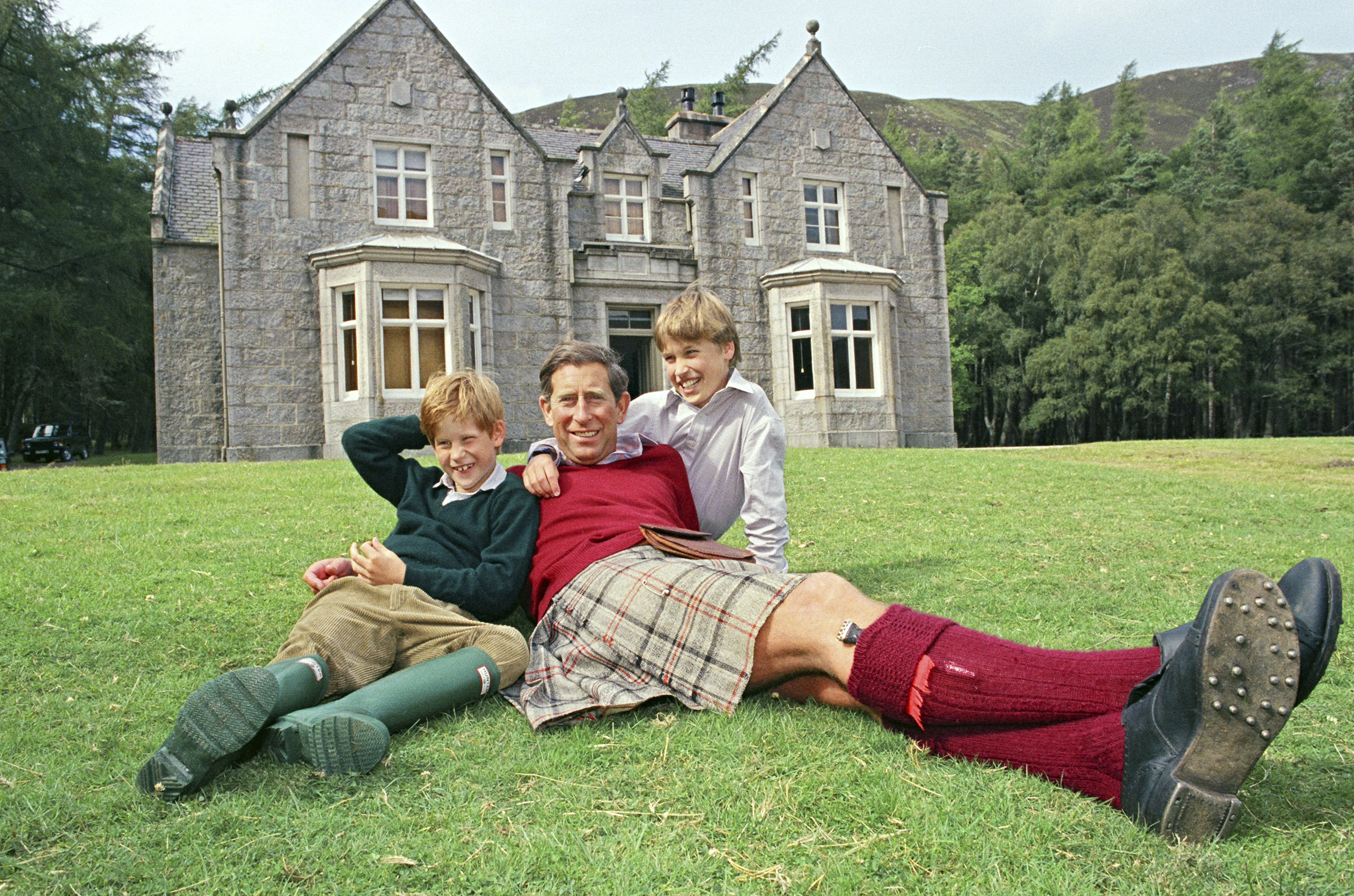 Charles and his sons relax on the lawn of Glas-allt Shiel, a royal lodge by the shores of a lake on the Balmoral estate in Scotland, in 1993.