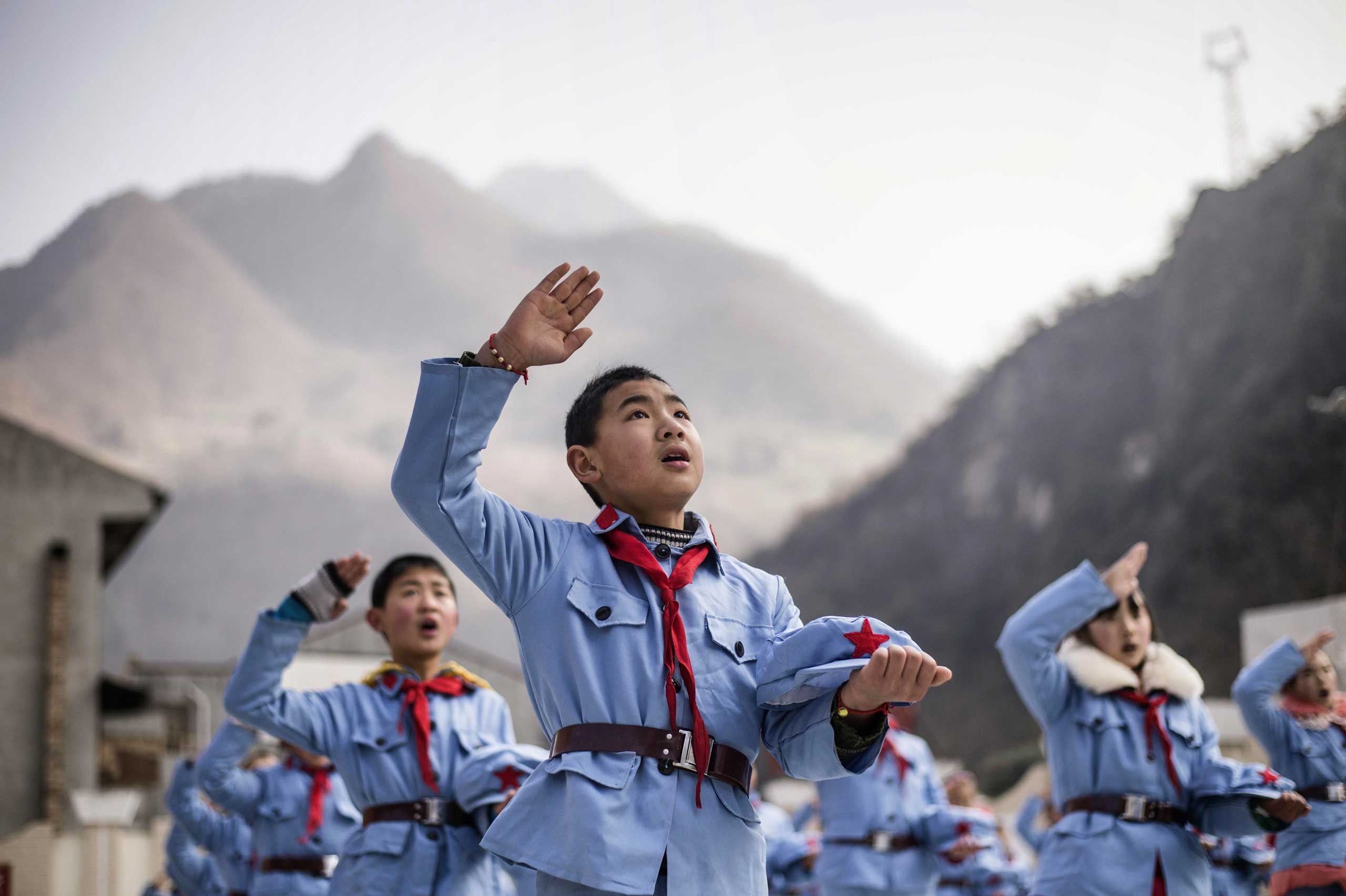 Children sing after raising the national flag.
