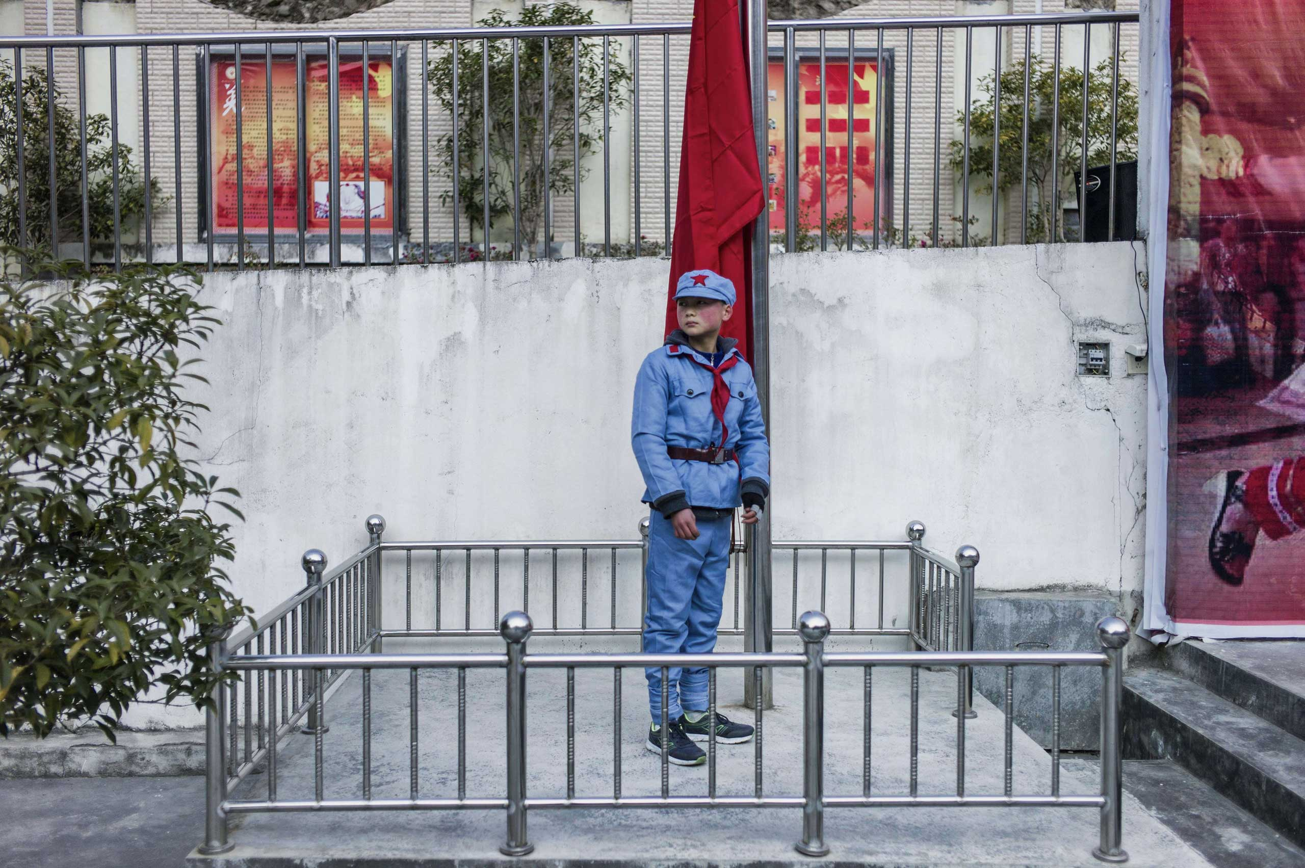 A child wearing a uniform waits to raise the national flag on Jan. 21, 2015 at the Beichuan Red army elementary school in Beichuan, southwest China's Sichuan province.