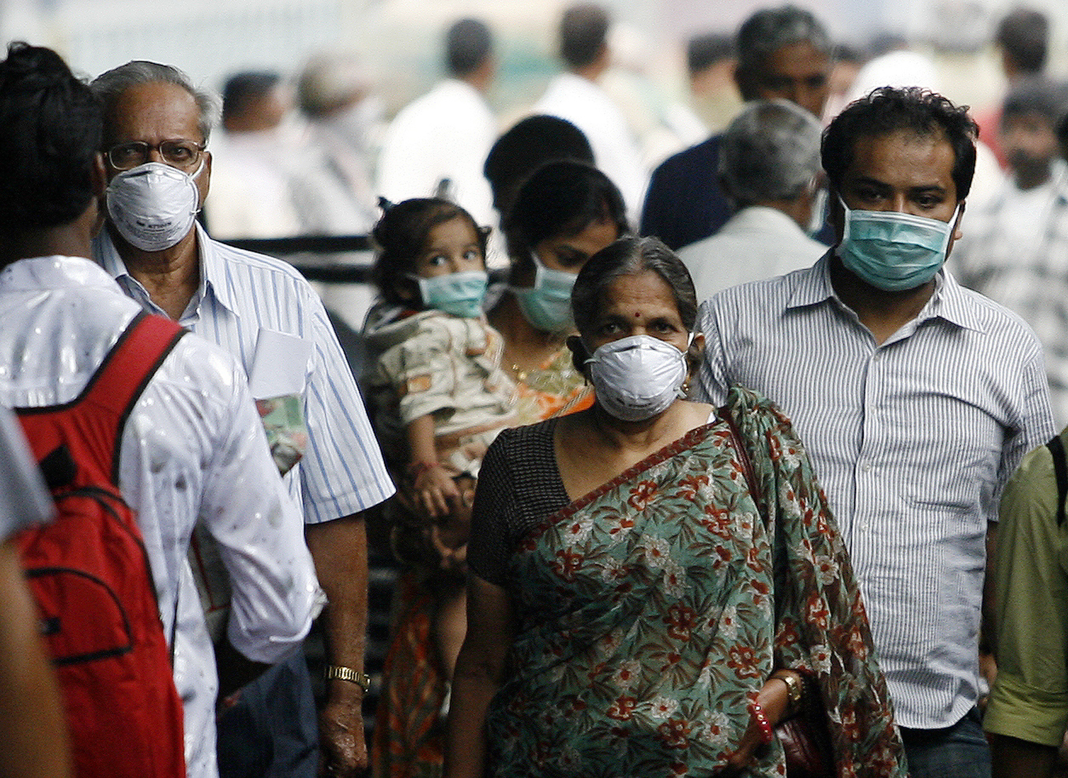 Travellers with masks walk on a railway platform in Pune August 18, 2009.