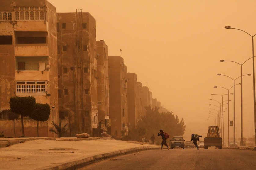 Young students run to their homes during a sandstorm in 6 October city, a suburb southwest of Cairo, Feb. 11, 2015.