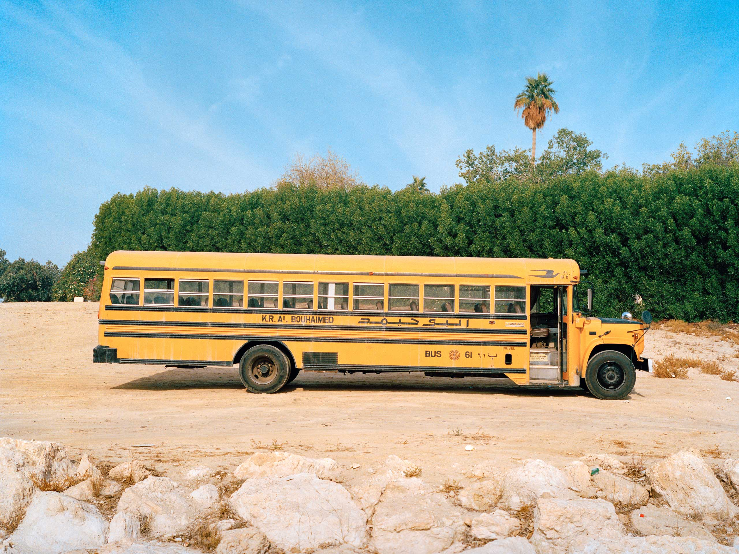 "A translplanted American ""Bluebird"" school bus is used to transport workers. These buses are a common site in Saudi Arabia. Some of them still have the name of the original American school district."