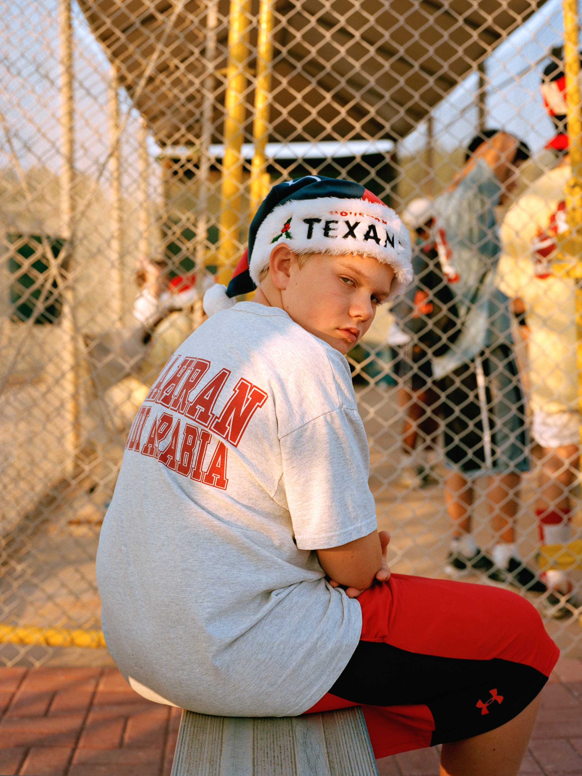 An onlooker wears his Texans Santa hat at the annual Returning Student Co-ed Softball game during Christmas time in Dhahran. Aramco schooling runs from kindergarten to ninth grade. After this time, schooling is generally continued overseas or in one of the nearby international schools.
