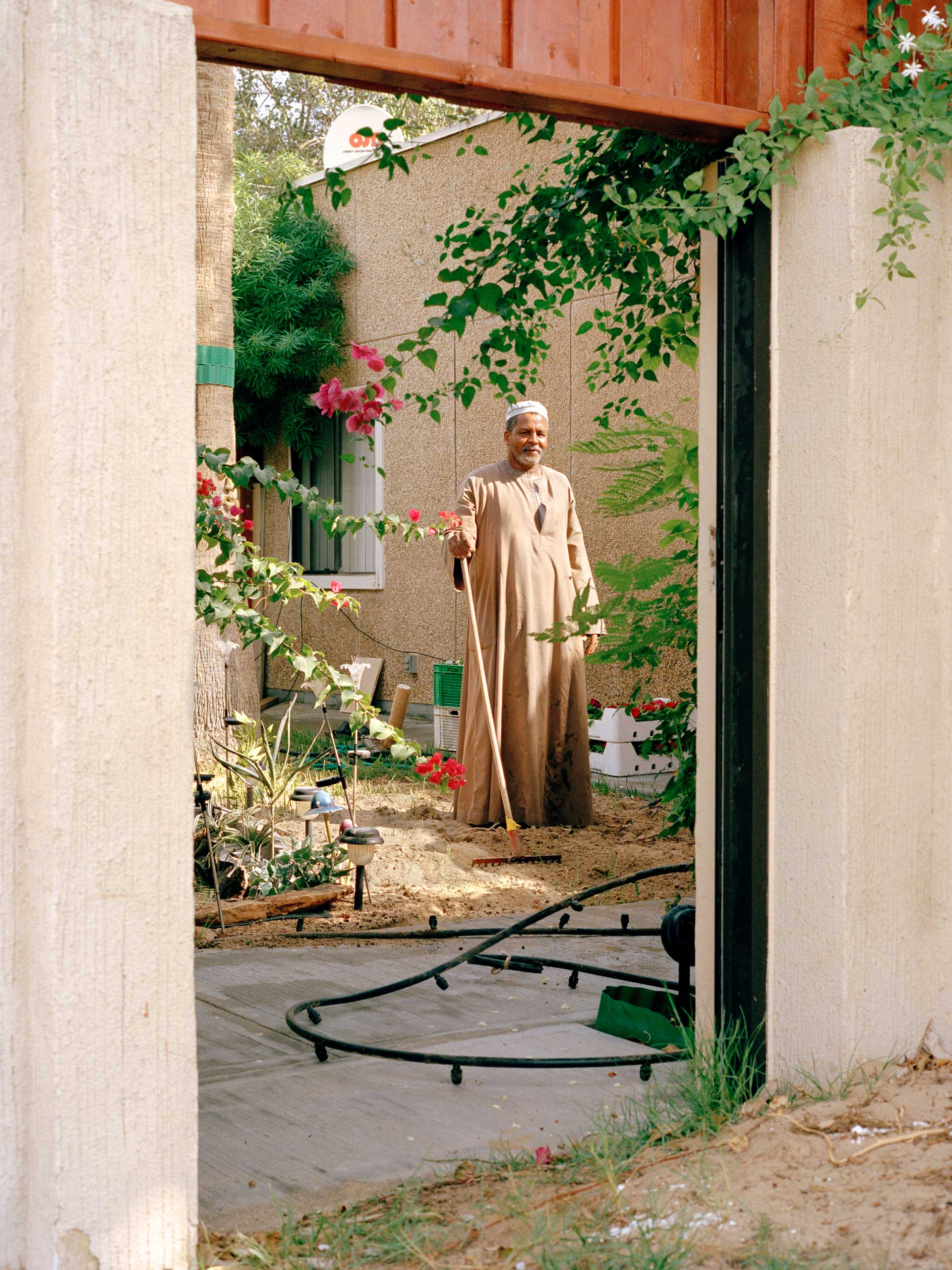 A gardner works in the backyard at a home in Dhahran.